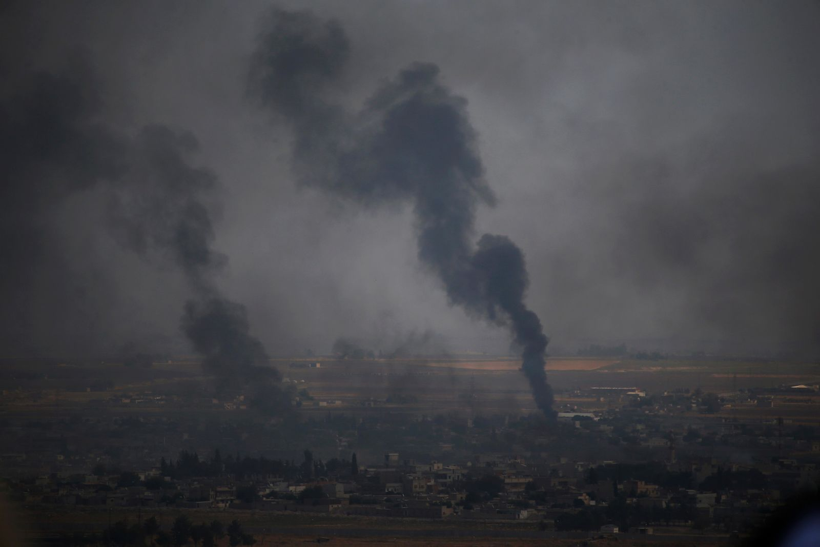 In this photo taken from the Turkish side of the border between Turkey and Syria, in Ceylanpinar, Sanliurfa province, southeastern Turkey, smoke billows from targets in Ras al-Ayn, Syria, during bombardment by Turkish forces, Wednesday, Oct. 16, 2019. Turkey's President Recep Tayyip Erdogan called Wednesday on Syrian Kurdish fighters to leave a designated border area in northeast Syria 'as of tonight' for Turkey to stop its military offensive, defying pressure on him to call a ceasefire and halt its incursion into Syria, now into its eighth day. (AP Photo/Lefteris Pitarakis)