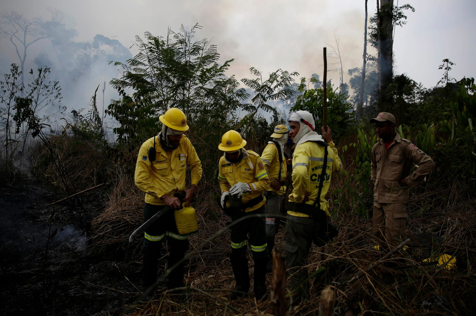 Firefighters rest briefly as they put out fires along the road to Jacunda National Forest, near the city of Porto Velho in the Vila Nova Samuel region which is part of Brazil's Amazon, Monday, Aug. 26, 2019.{ } (AP Photo/Eraldo Peres)