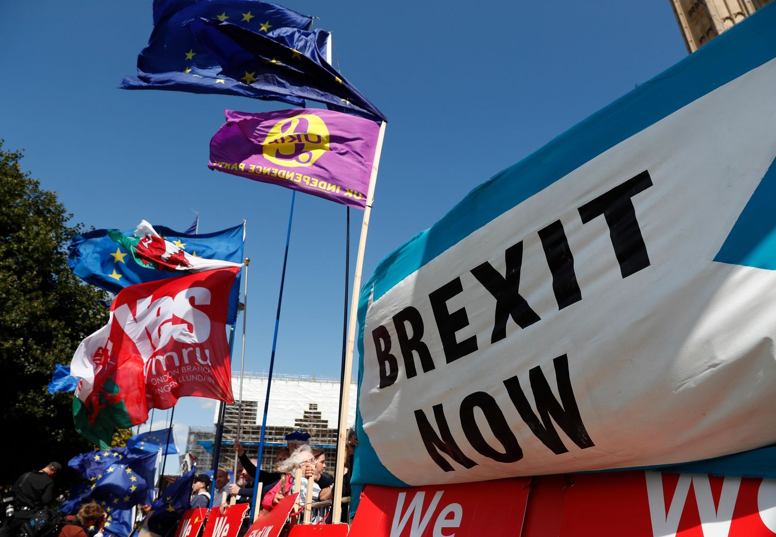 "Remain and leave supporters wave flags and hold banners during a demonstration outside the gates of Parliament in London, Wednesday, Sept. 4, 2019. With Britain's prime minister weakened by a major defeat in Parliament, defiant lawmakers were moving Wednesday to bar Boris Johnson from pursuing a ""no-deal"" departure from the European Union. (AP Photo/Alastair Grant)"