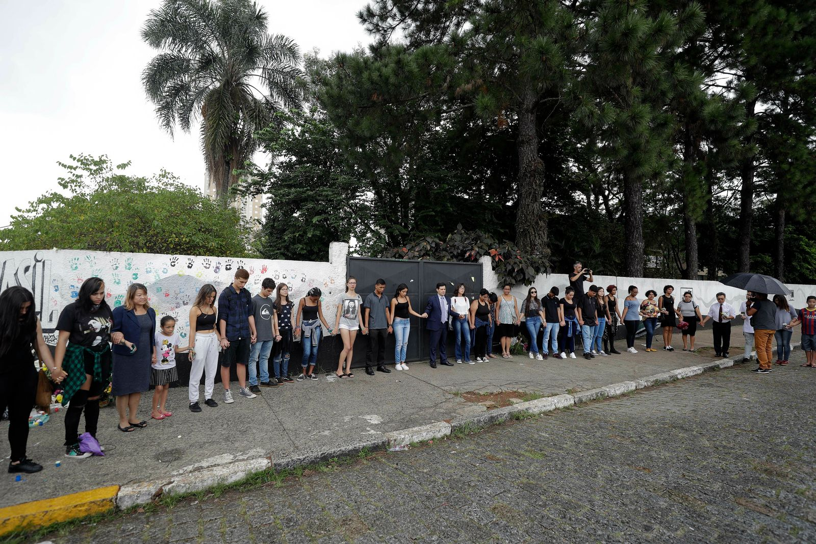 Students, relatives and neighborhood residents, pray outside the Raul Brasil State School one day after a mass shooting, in Suzano, Brazil, Thursday, March 14, 2019. (AP Photo/Andre Penner)