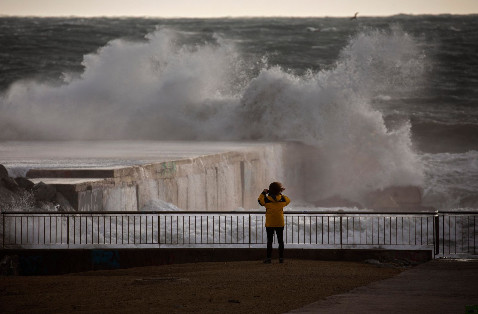 A woman photographs the Mediterranean sea during strong winds in Barcelona, Spain, Monday, Jan. 20, 2020.{ } (AP Photo/Emilio Morenatti)