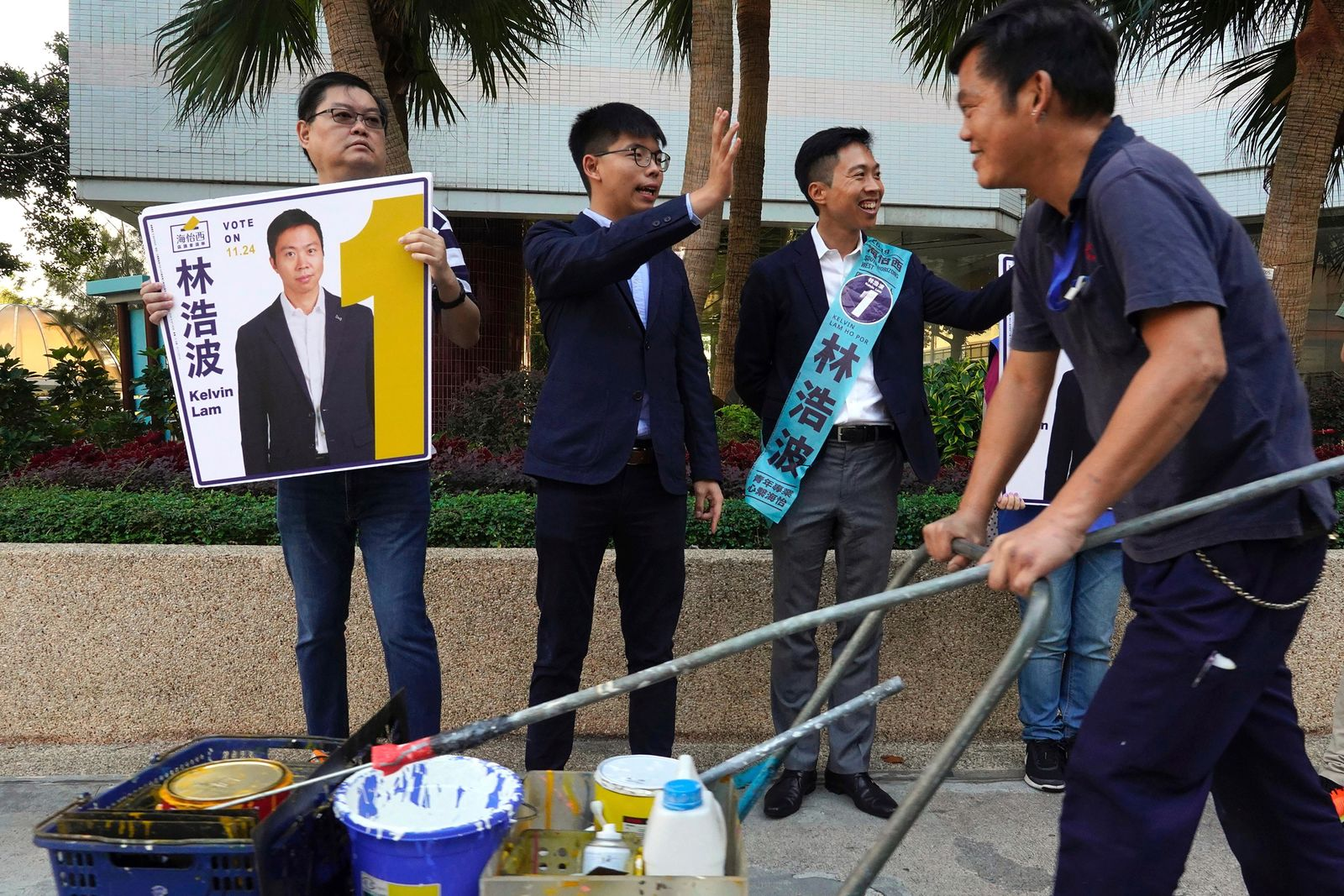 "Pro-democracy activist Joshua Wong, center, campaigns with local election candidate Kelvin Lam, right, in Hong Kong, Saturday, Nov. 23, 2019. Chanting ""No more tear gas,"" dozens of Hong Kong families with young children are marching to oppose the government's handling of protests on the eve of keenly contested local elections. (AP Photo/Vincent Yu)"