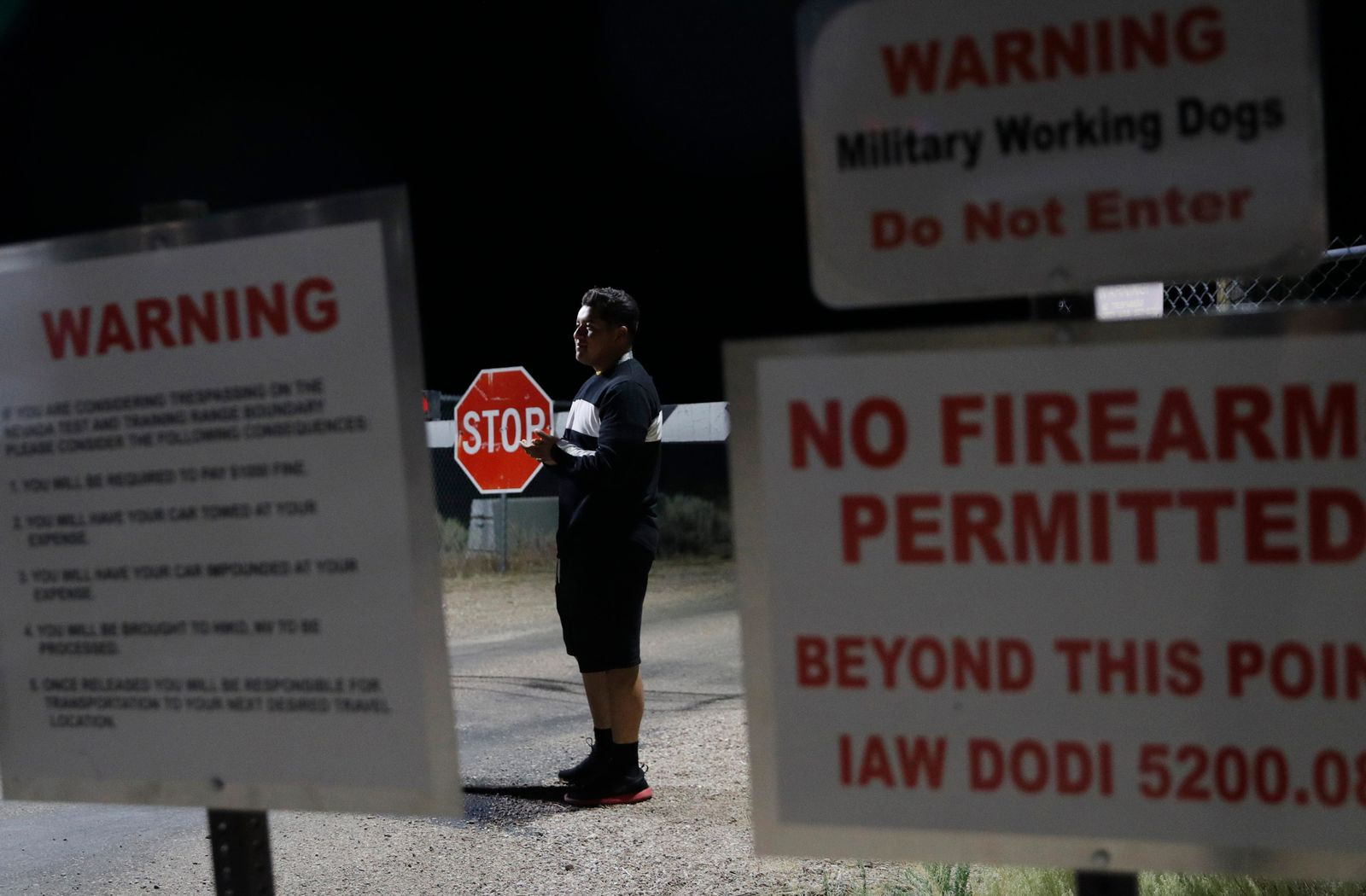 "A man stands at an entrance to the Nevada Test and Training Range near Area 51 Friday, Sept. 20, 2019, near Rachel, Nev. People gathered at the gate inspired by the ""Storm Area 51"" internet hoax. (AP Photo/John Locher)"