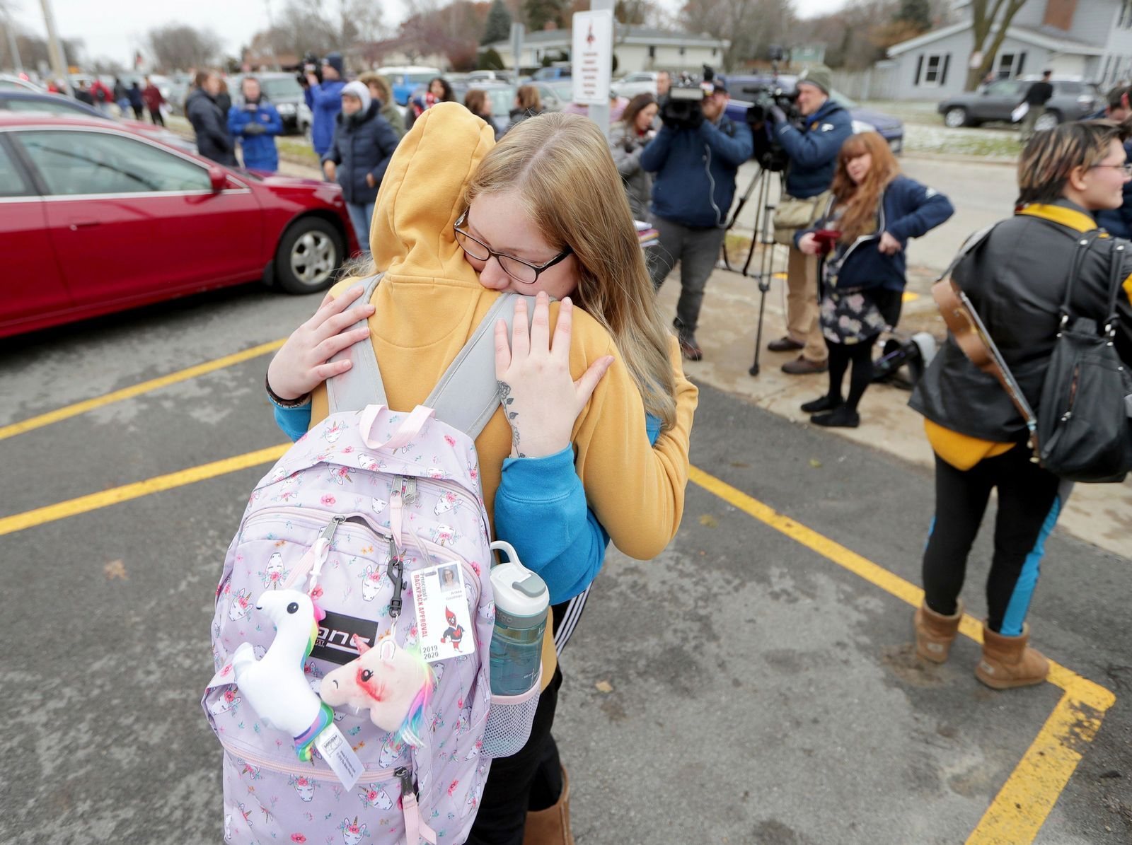 Alexis Grady, facing, a 17-year-old senior, hugs her friend Arissa Goodman outside Waukesha South High School in Waukesha, Wis., on Monday, Dec. 2, 2019.{ } (Mike De Sisti/Milwaukee Journal-Sentinel via AP)