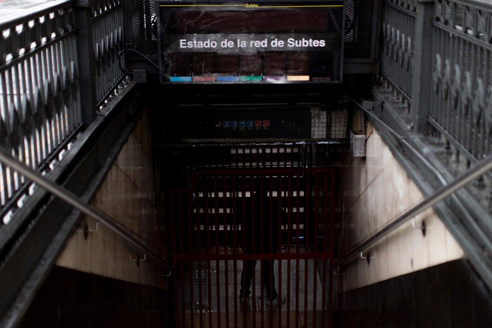 A subway employee stands in the closed entrance of the Buenos Aires's subway during a blackout, in Buenos Aires, Argentina, Sunday, June 16, 2019. Argentina and Uruguay were working frantically to return power on Sunday, after a massive power failure left large swaths of the South American countries in the dark.  (AP Photo/Tomas F. Cuesta)
