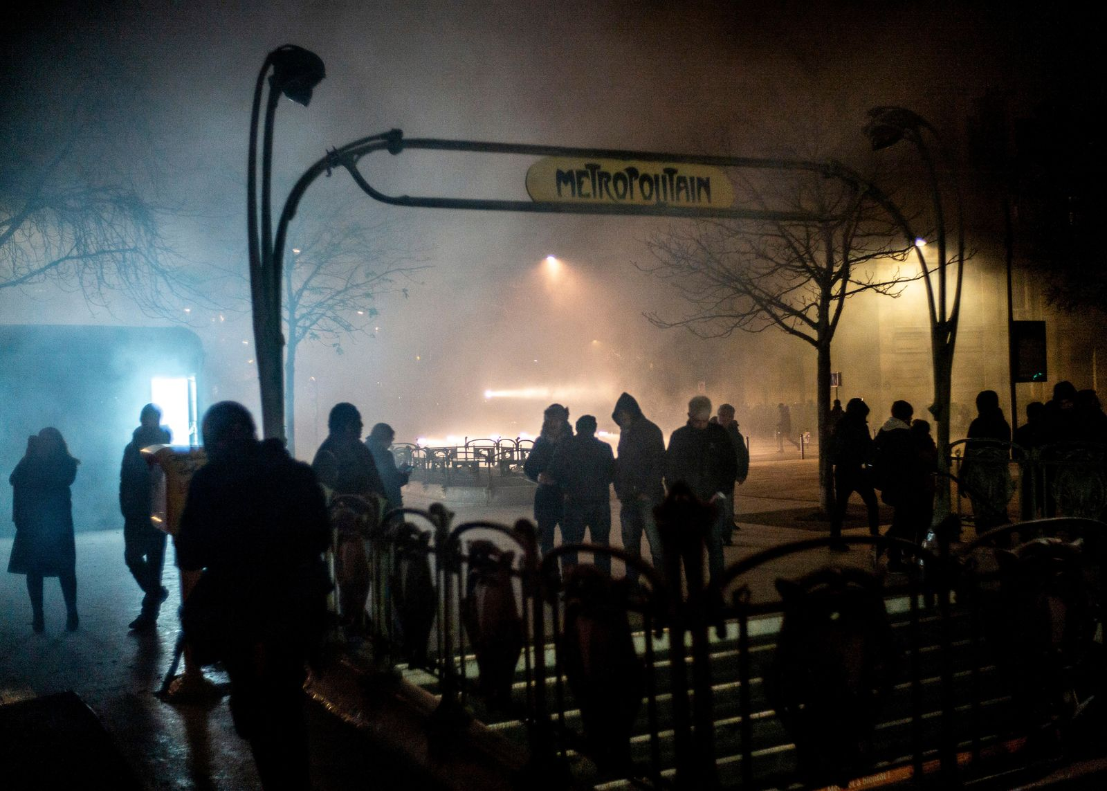 People stand next to the entrance of a metro station at the end of a demonstration in Paris, Thursday, Dec. 5, 2019. (AP Photo/Rafael Yaghobzadeh)