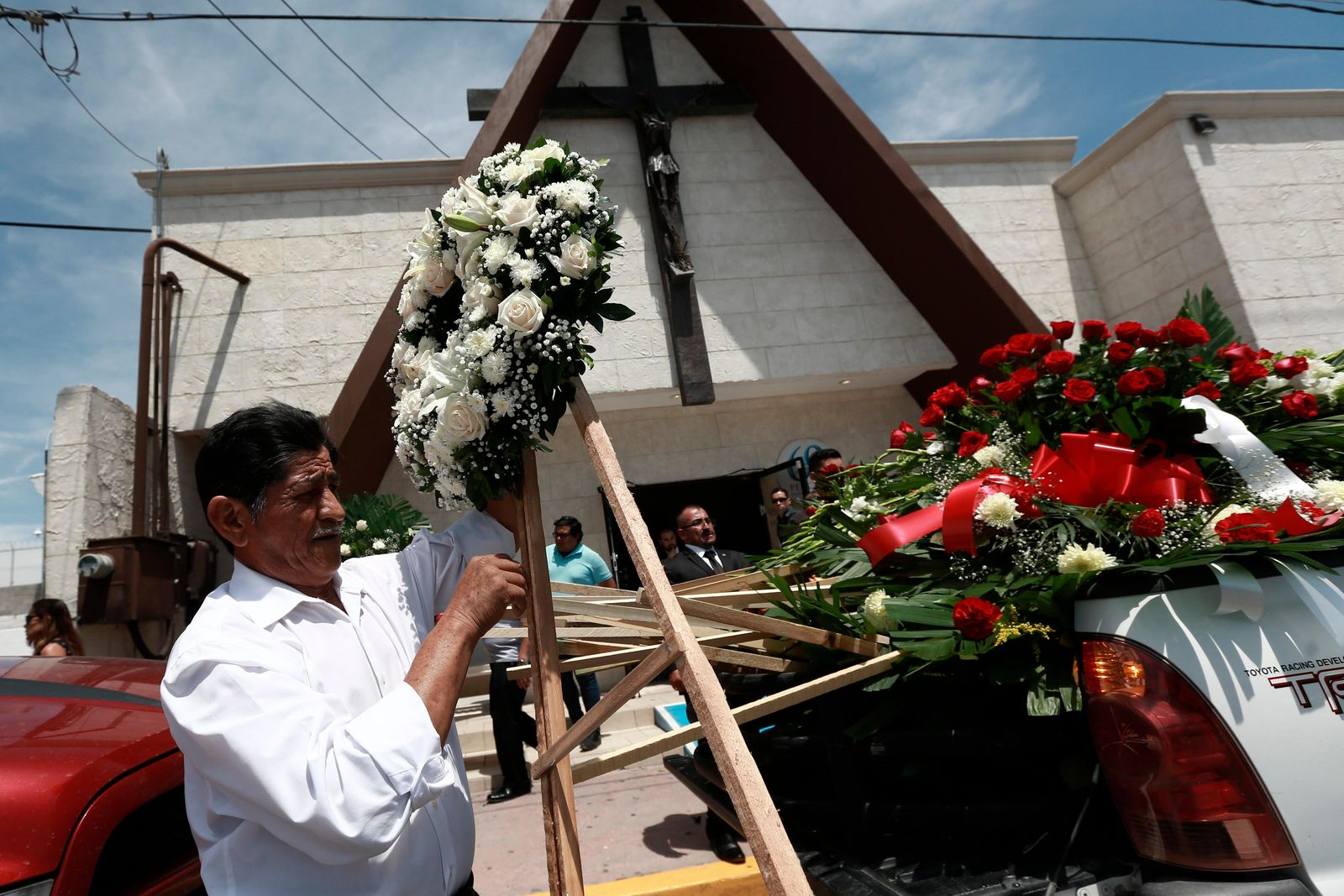 A man unloads funeral wreaths for a memorial service for Ivan Manzano, who was killed in the El Paso mass shooting, outside the Perches funeral home in Ciudad Juarez, Mexico, Friday, Aug. 9, 2019. Families of those killed when a gunman opened fire at an El Paso Walmart are gathering at funerals on each side of the U.S.-Mexico border to remember loved ones.  (AP Photo/Christian Chavez)