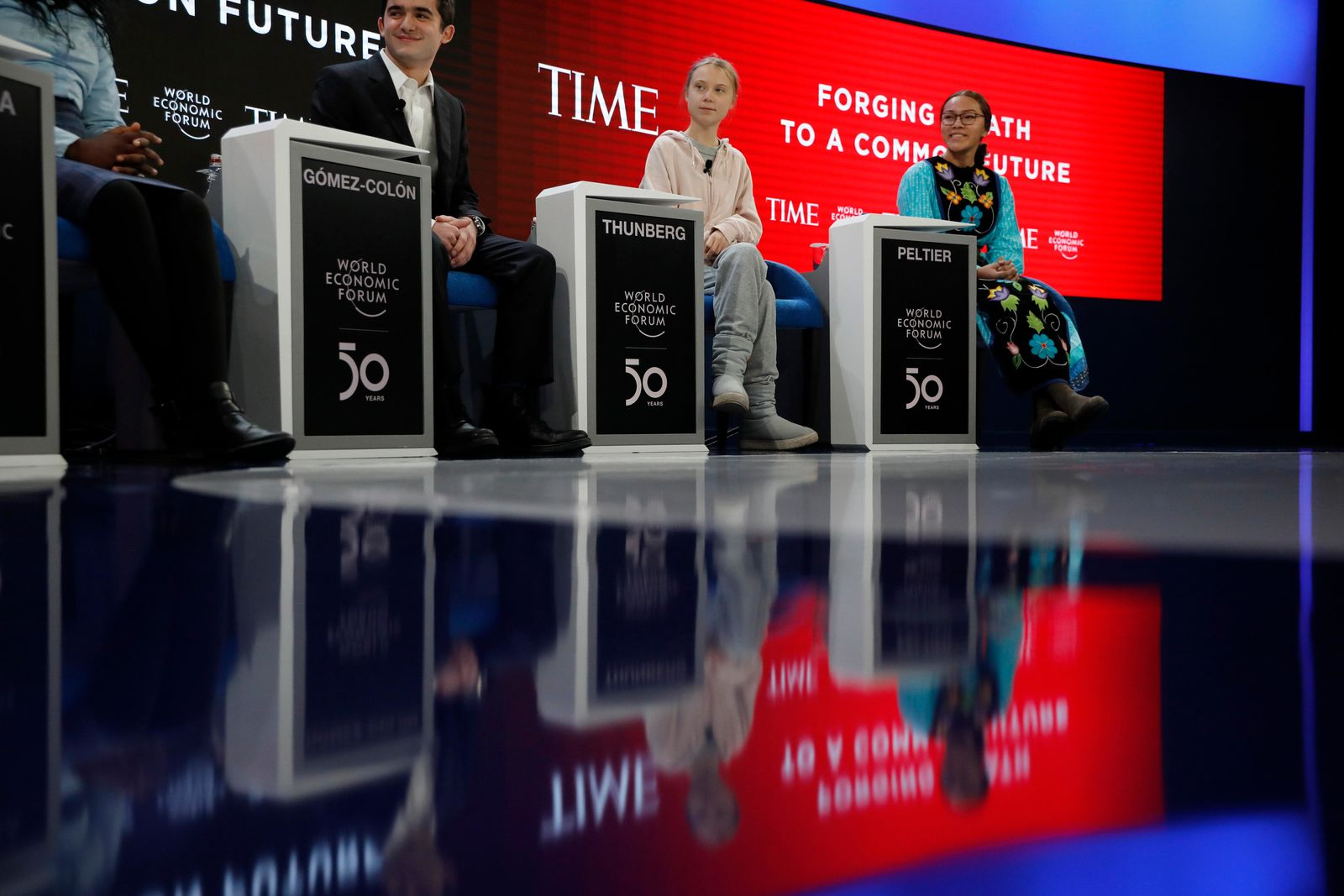 Swedish environmental activist Greta Thunberg, center, takes her seat prior to the opening session of the World Economic Forum in Davos, Switzerland, Tuesday, Jan. 21, 2020.{ } (AP Photo/Markus Schreiber)