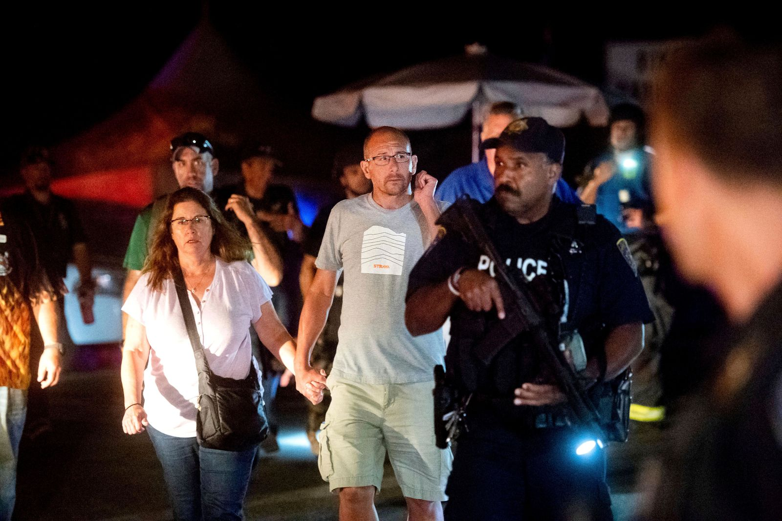 FILE - In this July 28, 2019, file photo, police officers escort people from Christmas Hill Park following a deadly shooting during the Gilroy Garlic Festival, in Gilroy, Calif. In the days and weeks since three high-profile shootings took the lives of more than two dozen people in just a week's time, law enforcement authorities have reported seeing a spike in the number of tips they are receiving from concerned relatives, friends and co-workers of people who appear bent on carrying out the next mass shooting. (AP Photo/Noah Berger, File)