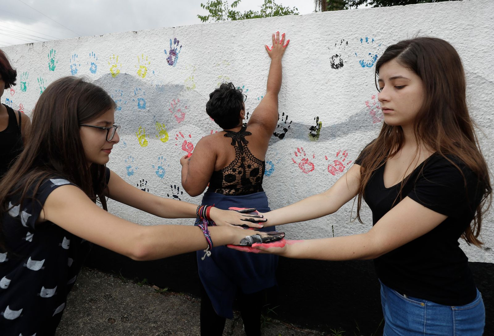 A student places her handprints on a wall at the Raul Brasil State School one day after a mass shooting, in Suzano, Brazil, Thursday, March 14, 2019. (AP Photo/Andre Penner)