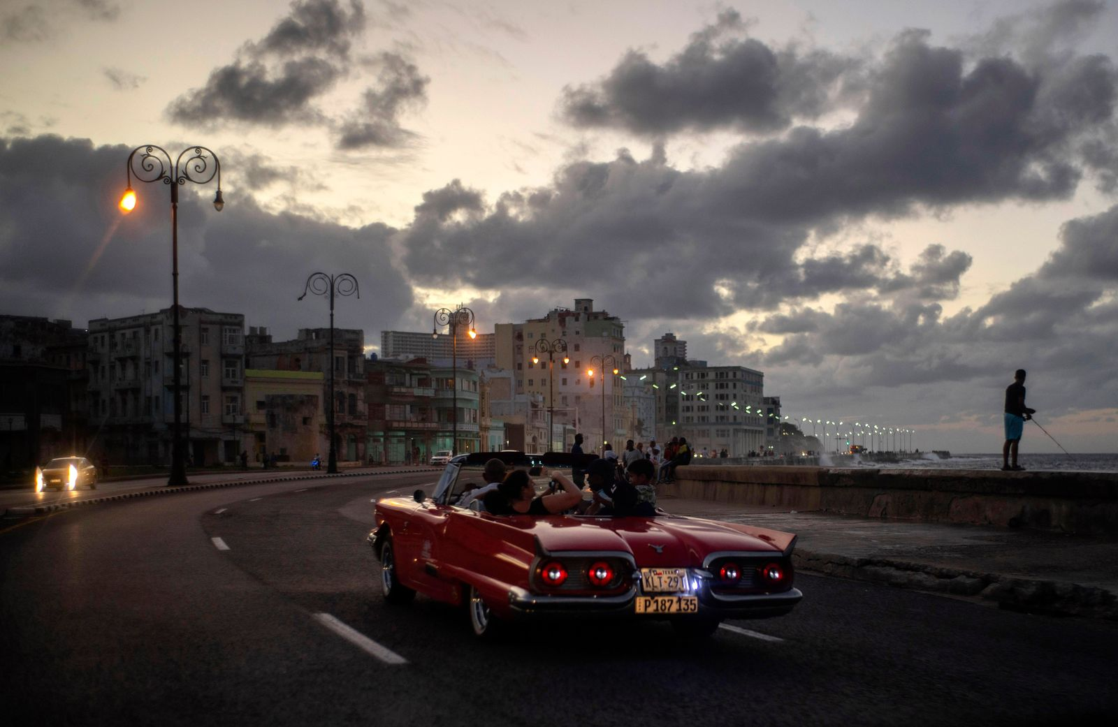 In this Nov. 10, 2019 photo, tourists take a joy ride along the malecon sea wall in Havana, Cuba. The city of Havana will celebrate its 500th anniversary on Nov. 16. (AP Photo/Ramon Espinosa)