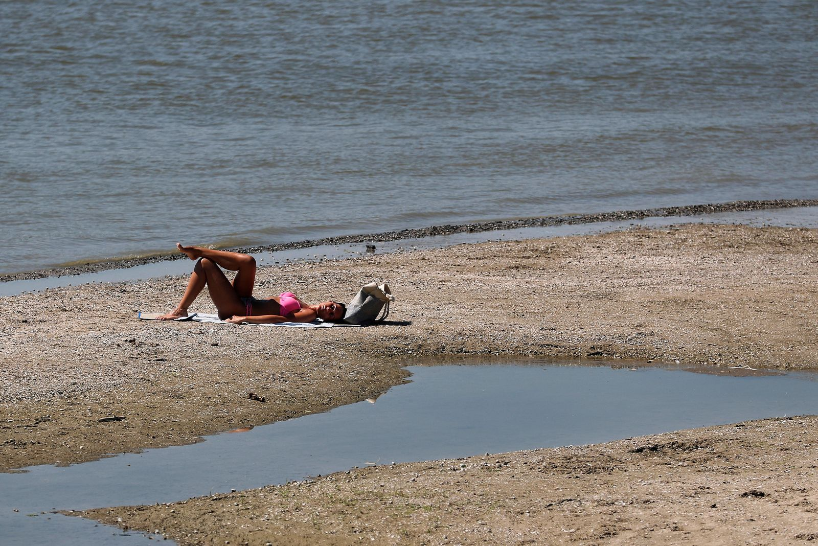 A woman sunbathes on the sandbank on Danube river in Belgrade, Serbia, Monday, Aug. 12, 2019. Hot weather has set in with temperatures rising up to 37 Celsius (98,6 Fahrenheit) in Serbia. (AP Photo/Darko Vojinovic)
