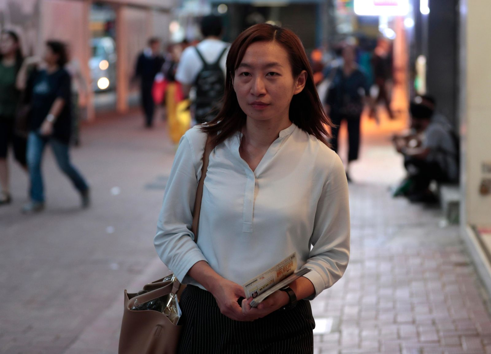 In this photo taken Thursday, Nov. 7, 2019, district council candidate Cathy Yau walks during her campaign at Causeway Bay in Hong Kong. (AP Photo/Dita Alangkara)