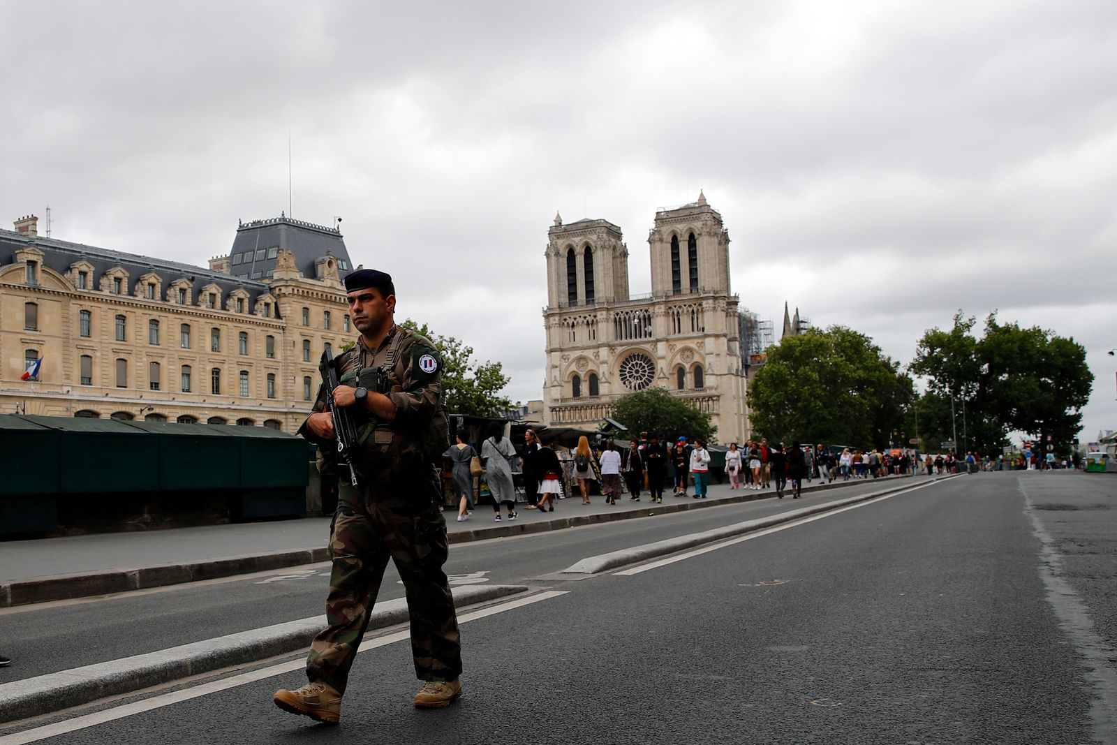 French soldier patrols as Catholic pilgrims take part in an emotional procession with the statue of the Virgin Mary rescued from the April blaze past the fire-ravaged Notre Dame Cathedral to celebrate the Assumption of the Virgin in Paris, Thursday, Aug. 15, 2019. (AP Photo/Francois Mori)