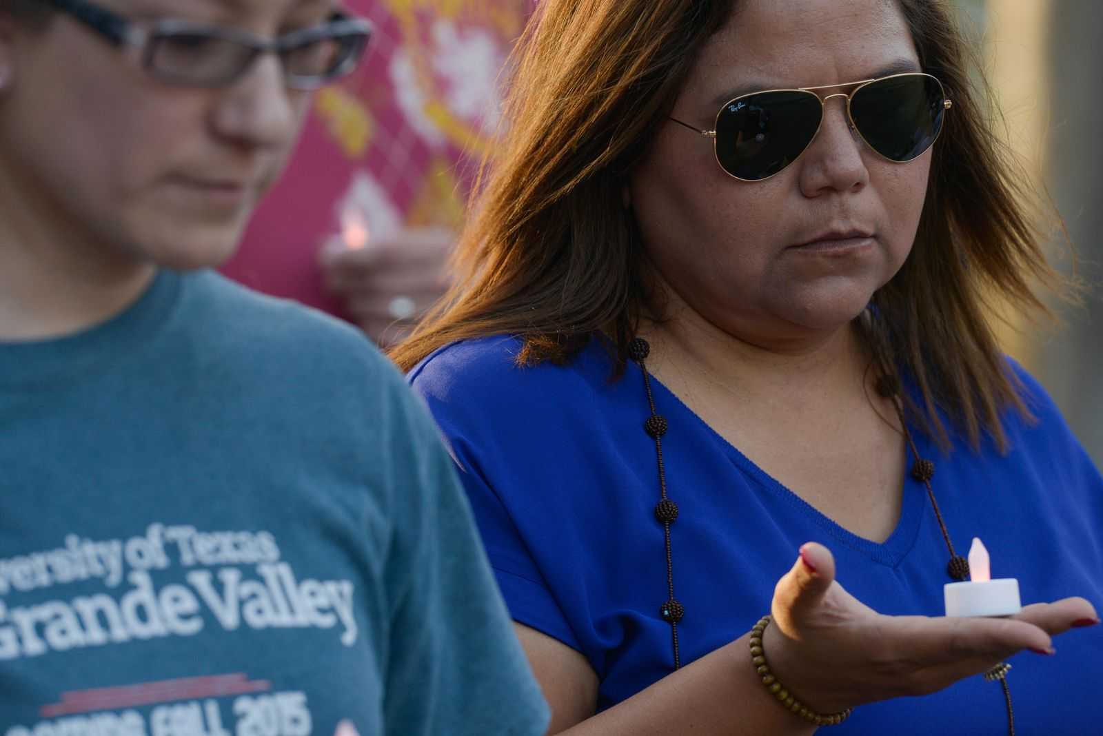 Celia Hernandez holds her candle in the palm of her hand during a moment of silence for the 22 victims of the recent El Paso shooting during a vigil Sunday, Aug. 11, 2019, at Alice Wilson Hope Park in Brownsville, Texas.(Denise Cathey/The Brownsville Herald via AP)