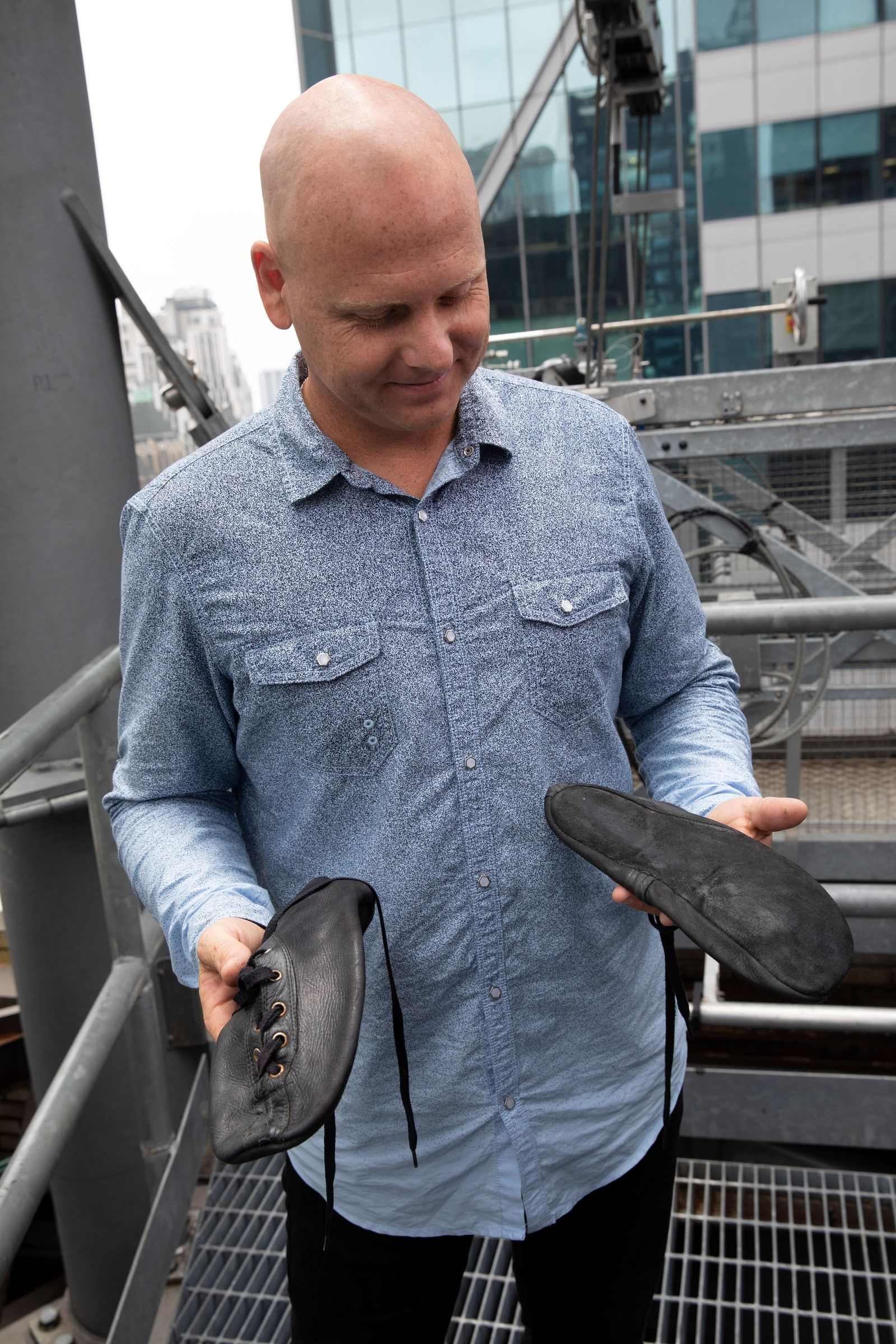 Aerialist Nik Wallenda talks with the media about his planned high-wire act, Thursday, June 20, 2019 in New York. Wallenda and his sister Lijana will cross Times Square on a high wire on Sunday. He is holding the shoes that he will wear. (AP Photo/Mark Lennihan)