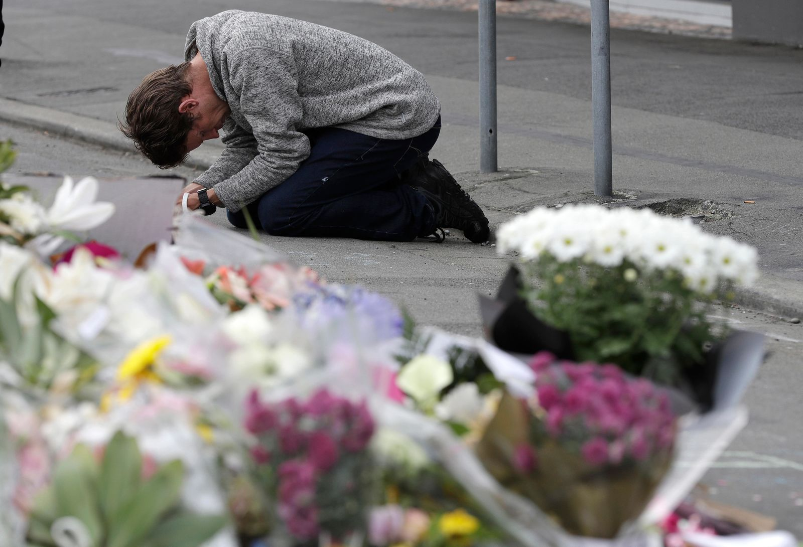 A mourner prays near the Linwood mosque in Christchurch, New Zealand, Tuesday, March 19, 2019. (AP Photo/Mark Baker)