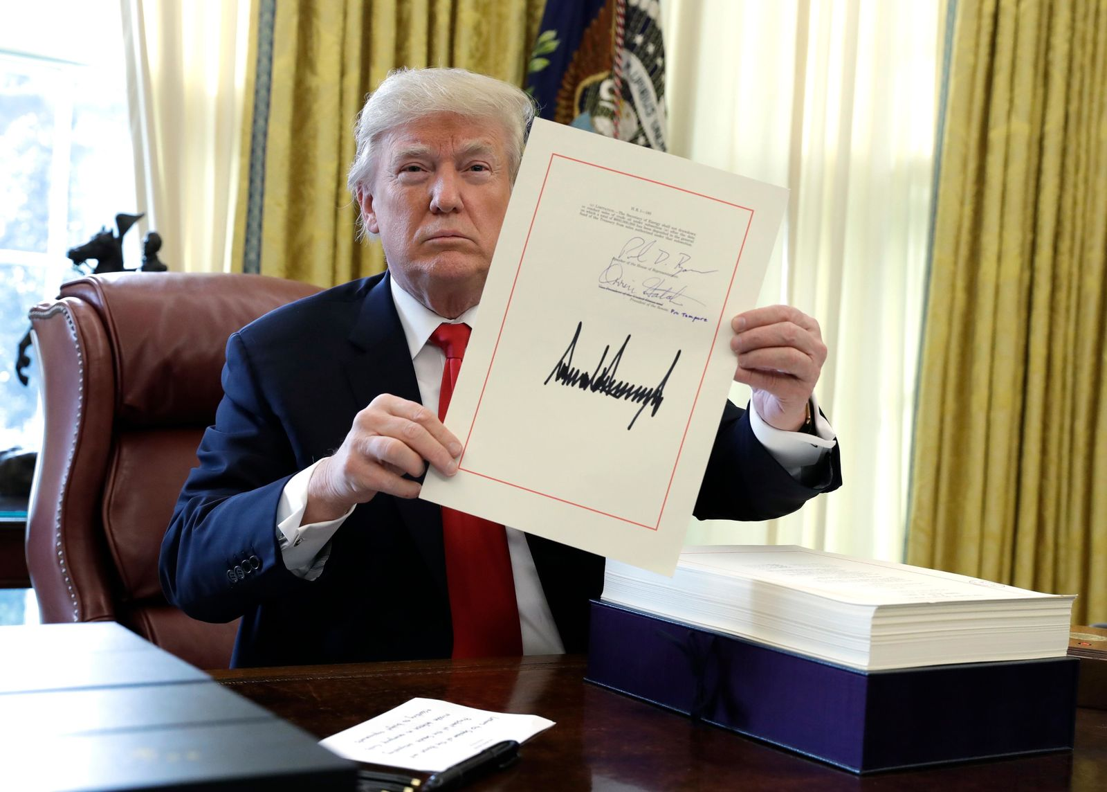 FILE - In this Dec. 22, 2017, file photo, President Donald Trump displays the $1.5 trillion tax overhaul package he signed in the Oval Office of the White House in Washington. Trump is now three for three. Each year of his presidency, he has issued more executive orders than did former President Barack Obama during the same time-span. (AP Photo/Evan Vucci, File)
