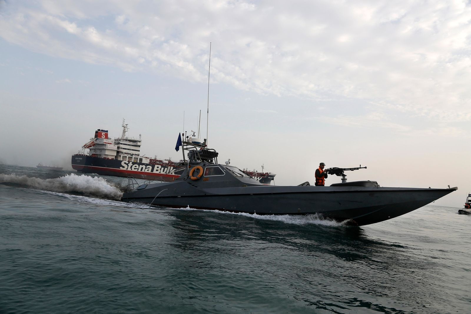 FILE- In this July 21, 2019 file photo, a speedboat of the Iran's Revolutionary Guard moves around a British-flagged oil tanker Stena Impero, which was seized on Friday by the Guard, in the Iranian port of Bandar Abbas. (Hasan Shirvani/Mizan News Agency via AP, File)