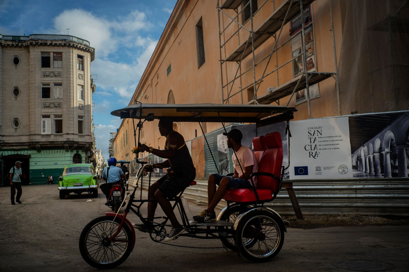 In this Nov. 9, 2019 photo, a bicycle taxi driver navigates his client past buildings under restoration in Havana, Cuba. The city will celebrate its 500th anniversary on Nov. 16. (AP Photo/Ramon Espinosa)