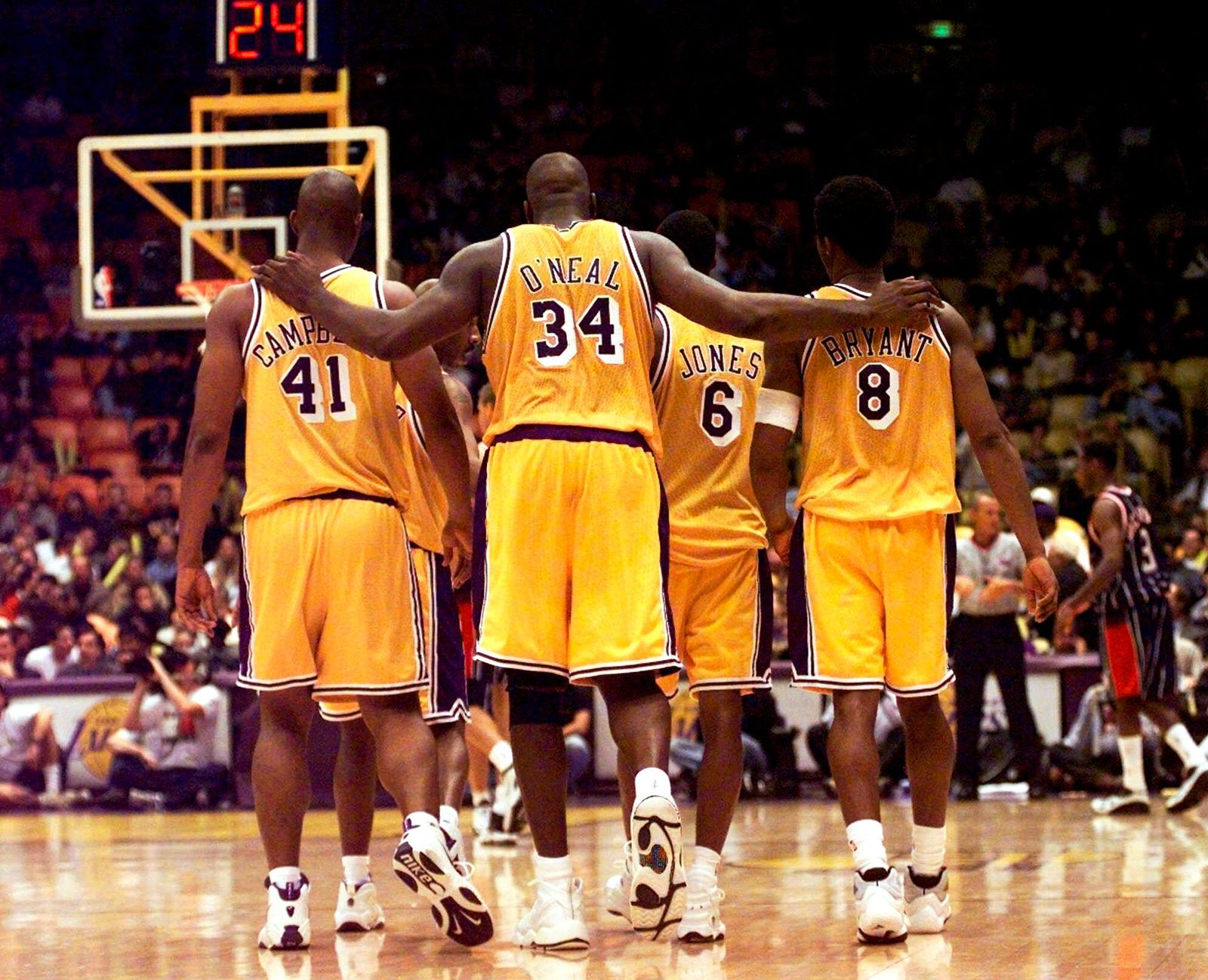 FILE - In this Feb. 5, 1999, file photo, Los Angeles Lakers center Shaquille O'Neal (34) puts his arms around teammates, Elden Campbell (41) and Kobe Bryant (8) as Eddie Jones (6) and Derek Harper walk in front as they return to play the Houston Rockets in the fourth quarter at the Great Western Forum in Inglewood, Calif. Bryant, the 18-time NBA All-Star who won five championships and became one of the greatest basketball players of his generation during a 20-year career with the Los Angeles Lakers, died in a helicopter crash Sunday, Jan. 26, 2020. (AP Photo/ Victoria Arocho, File)
