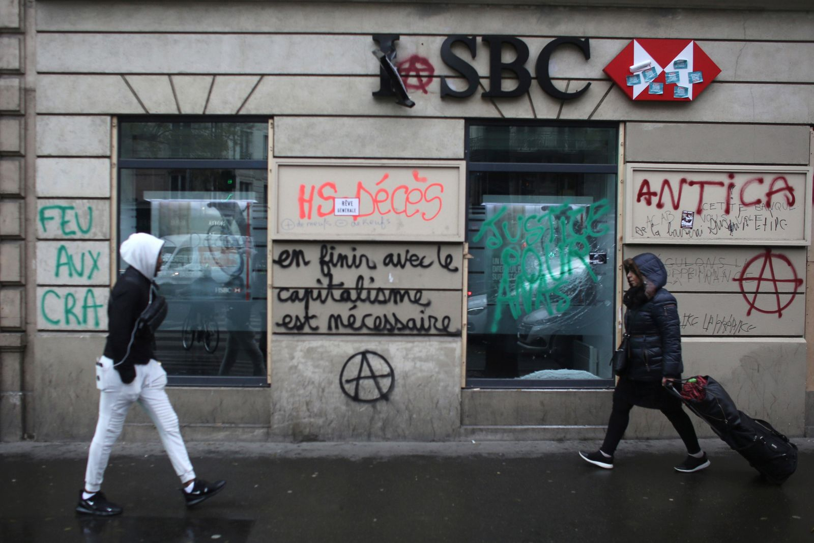People walk past a vandalized bank after Thursday's violence, Friday, Dec. 6, 2019 in Paris.(AP Photo/Rafael Yaghobzadeh)