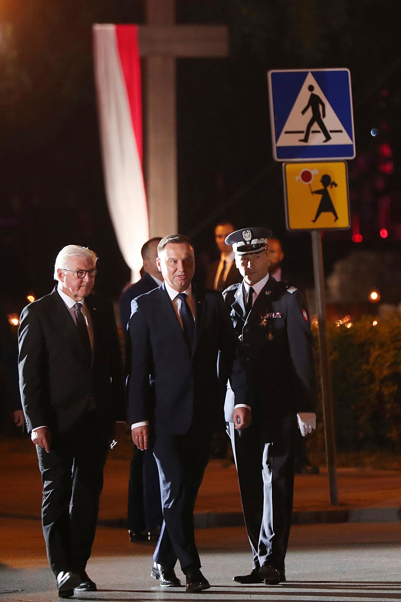 German President Frank-Walter Steinmeier, left, and Polish President Andrzej Duda, center, attend a ceremony marking the 80th anniversary of the start of World War II, in Wielun, Poland, Sunday, Sept. 1, 2019. The ceremony started at 4.40 a.m., the exact hour that, according to survivors, the war's first bombs fell, killing civilians. (AP Photo/Czarek Sokolowski)