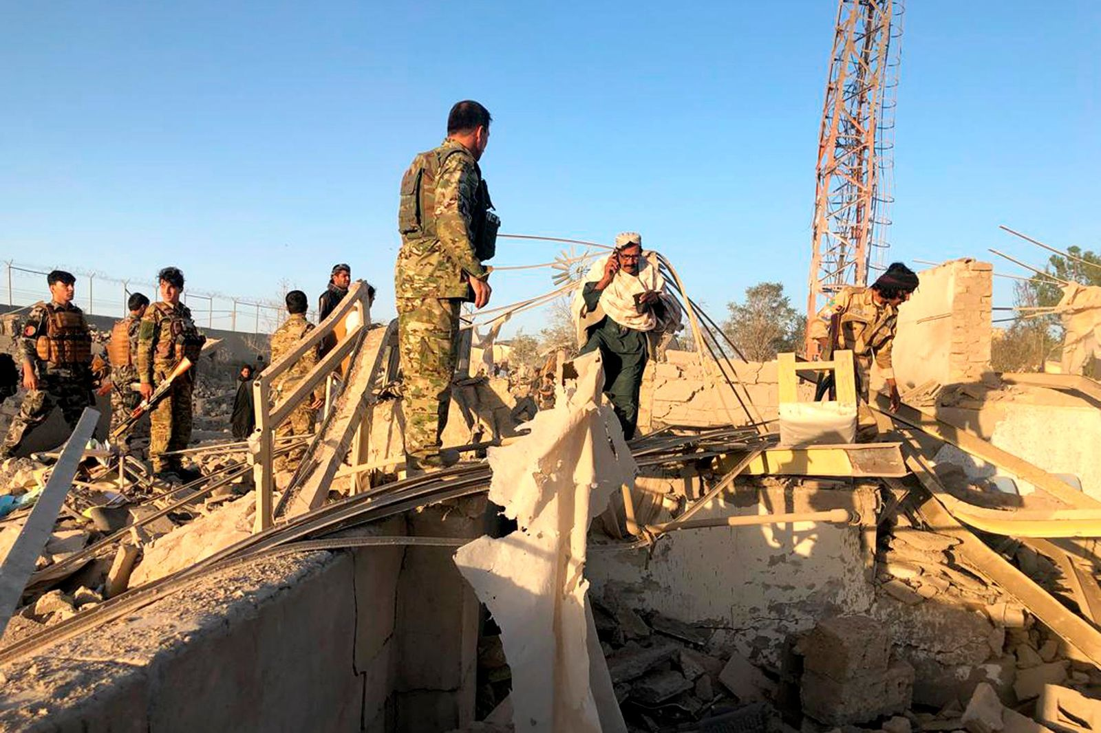 Afghan security members and people work at the site of a suicide attack in Zabul, Afghanistan, Thursday, Sept. 19, 2019. (AP Photo/Ahmad Wali Sarhadi)