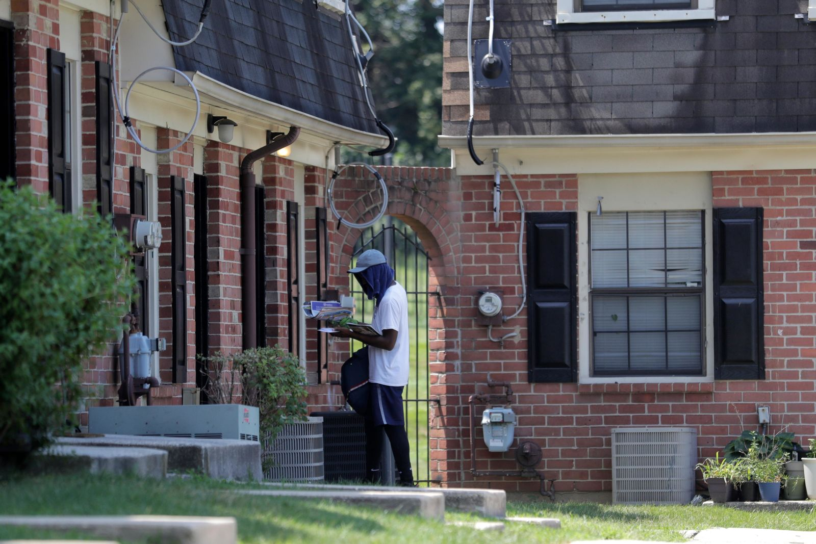 A mail carrier delivers mail at a home at the Dutch Village apartments, Tuesday, July 30, 2019, in Baltimore. (AP Photo/Julio Cortez)