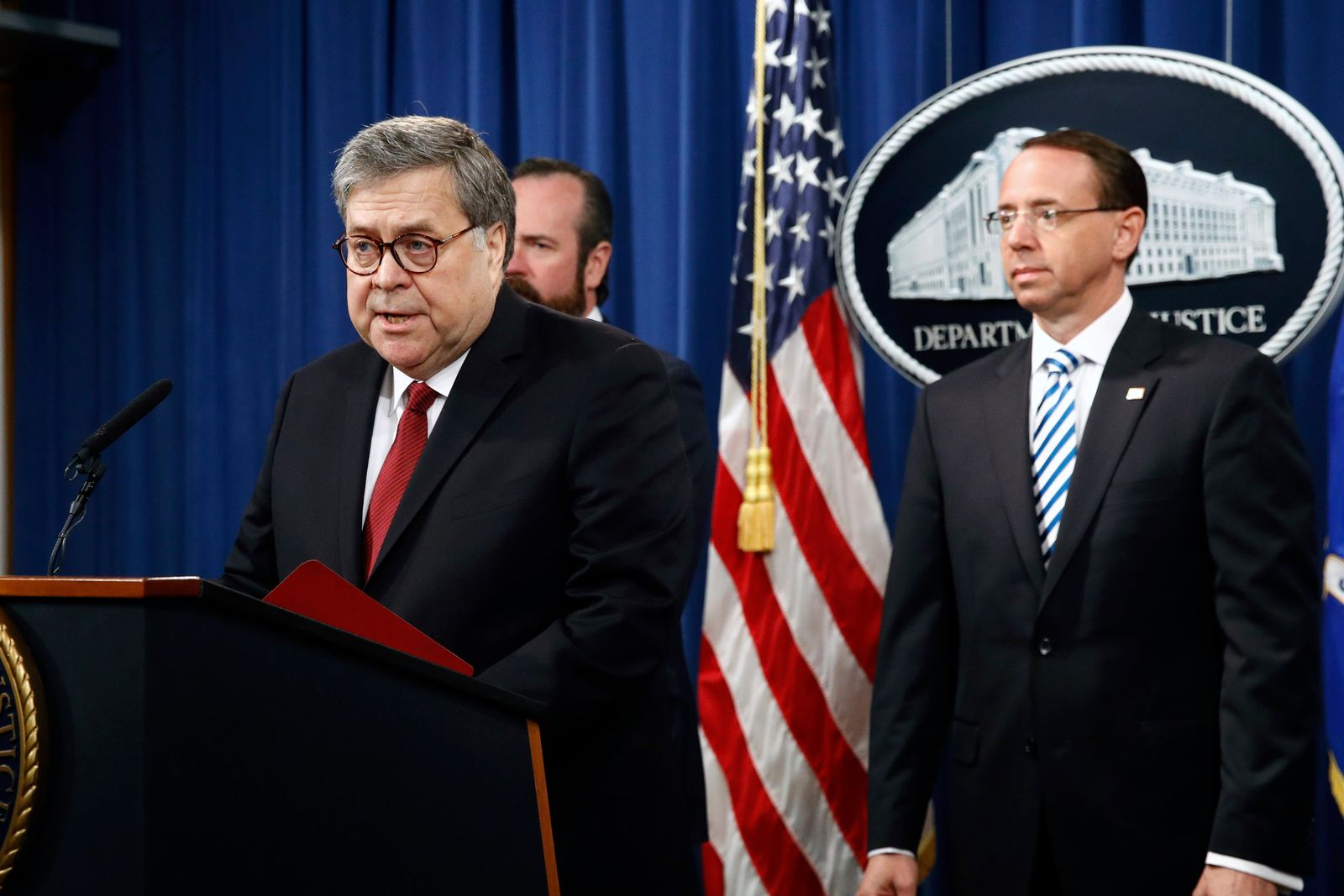 Attorney General William Barr speaks alongside Deputy Attorney General Rod Rosenstein, right, and acting Principal Associate Deputy Attorney General Edward O'Callaghan, rear left, about the release of a redacted version of special counsel Robert Mueller's report during a news conference, Thursday, April 18, 2019, at the Department of Justice in Washington. (AP Photo/Patrick Semansky)