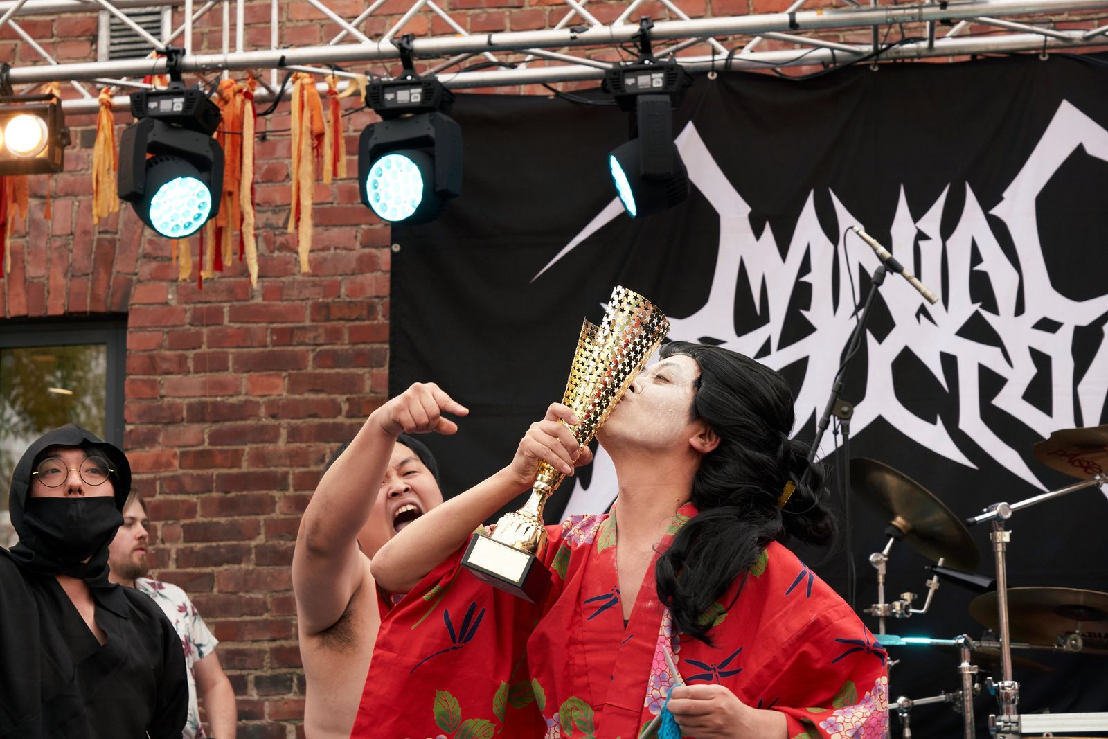 The Japanese team Giga Body Metal react with the trophy after being crowned Heavy Metal Knitting world champions with a show featuring crazy sumo wrestlers and team-leader Manabu Kaneko dressed in a traditional Japanese kimono knitting, Thursday, July 11, 2019 in Joensuu, Finland. (AP Photo/David Keyton)