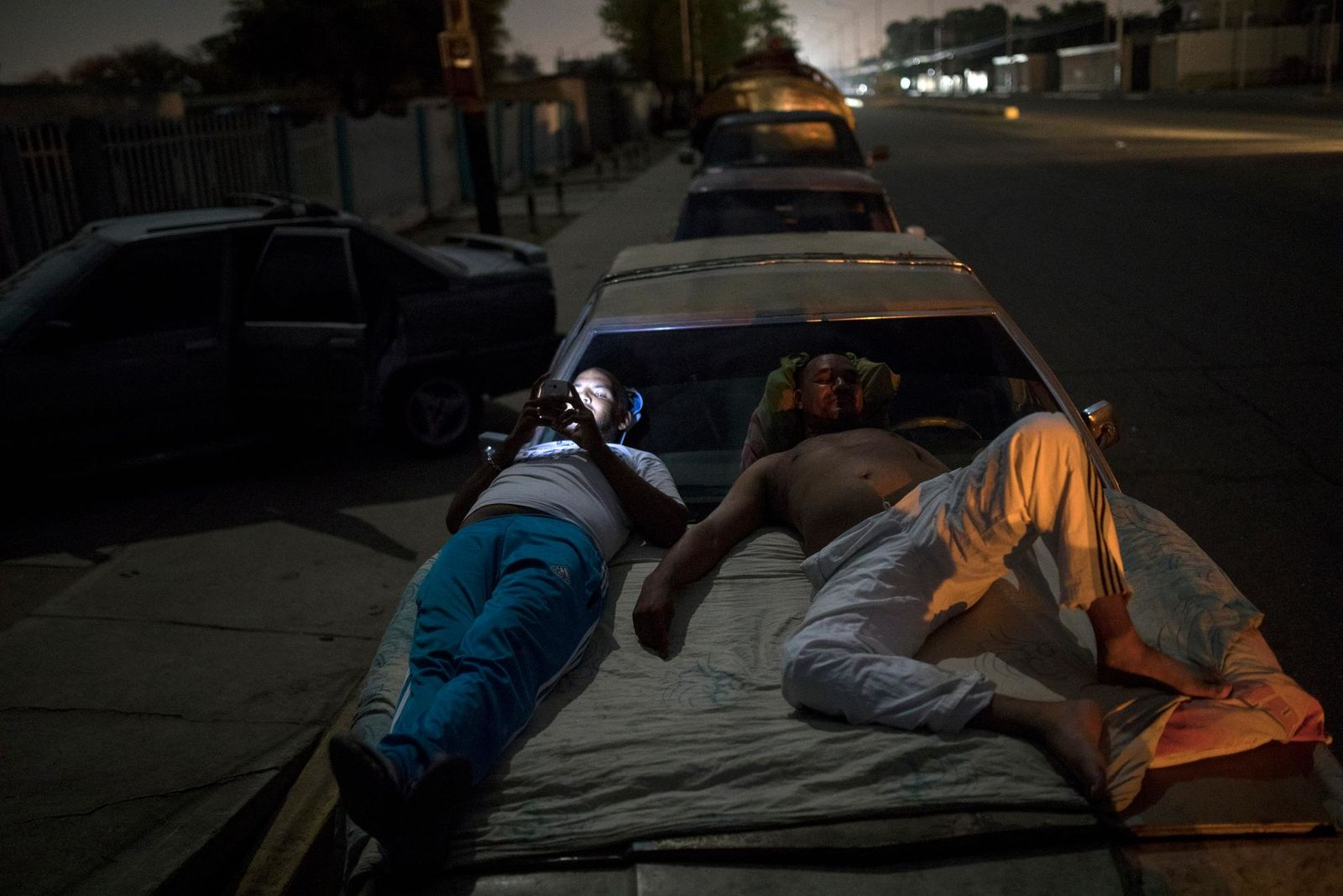 Andres Quintero, left, and Fermin Perez rest on top of Perez's car as they wait in line for over 20 hours to fill their tanks with gas in Cabimas, Venezuela, Thursday, May 16, 2019. (AP Photo/Rodrigo Abd)