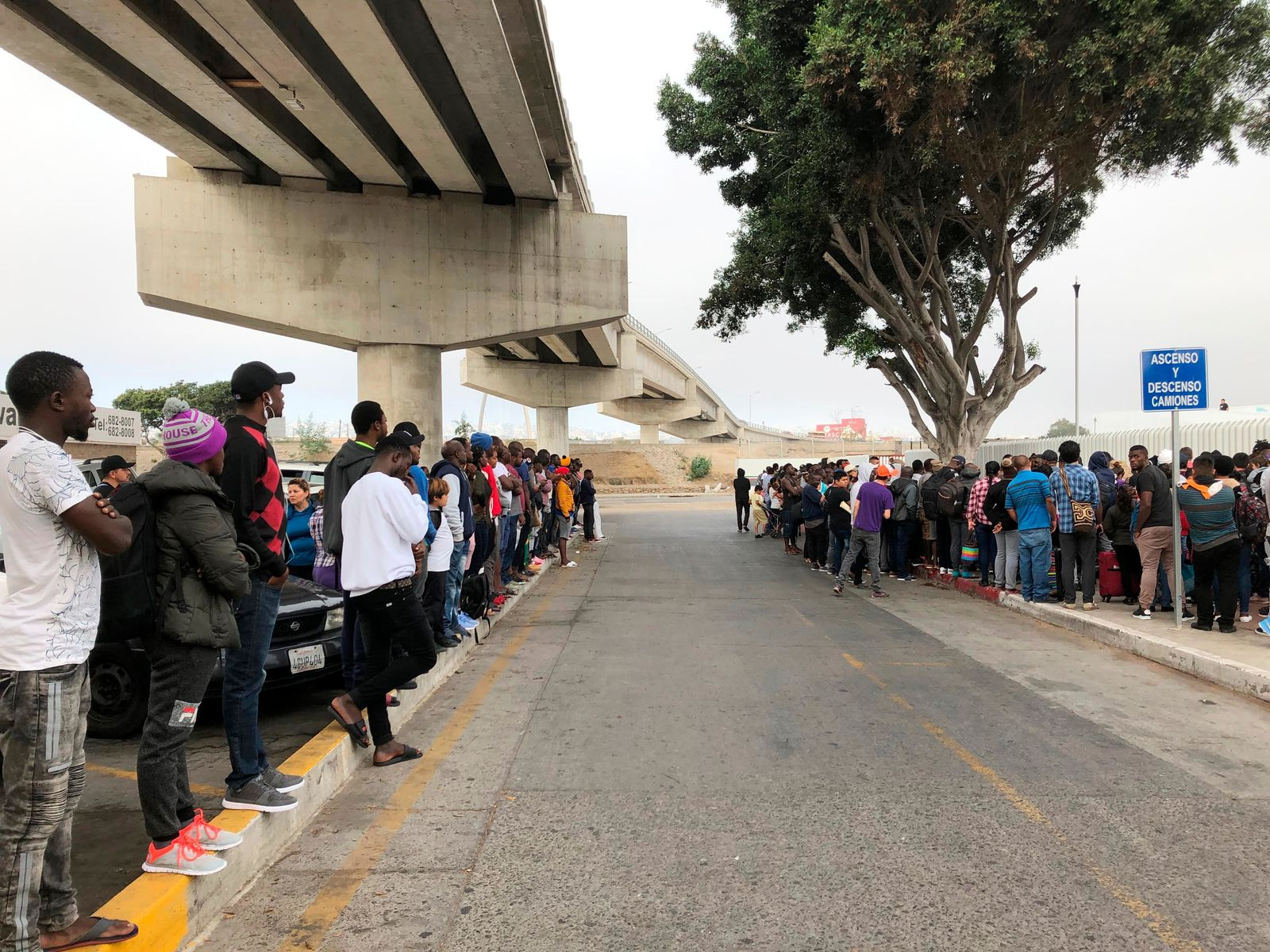 In this July 26, 2019 photo, a group of migrants in Tijuana, Mexico, listen to numbers being called for people to claim asylum in the U.S. The long waits are starting to test the patience of immigrants and border towns. (AP Photo/Elliot Spagat)