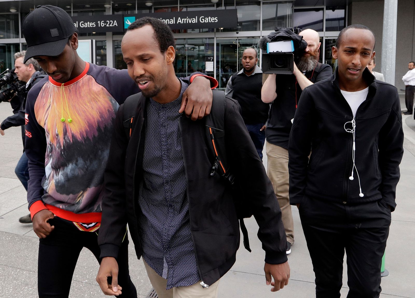 Abdifatah Ibrahim, center, and his brother Abdi, right, walk with an unidentified friend in Christchurch, New Zealand, Sunday, March 17, 2019.{ } (AP Photo/Mark Baker)