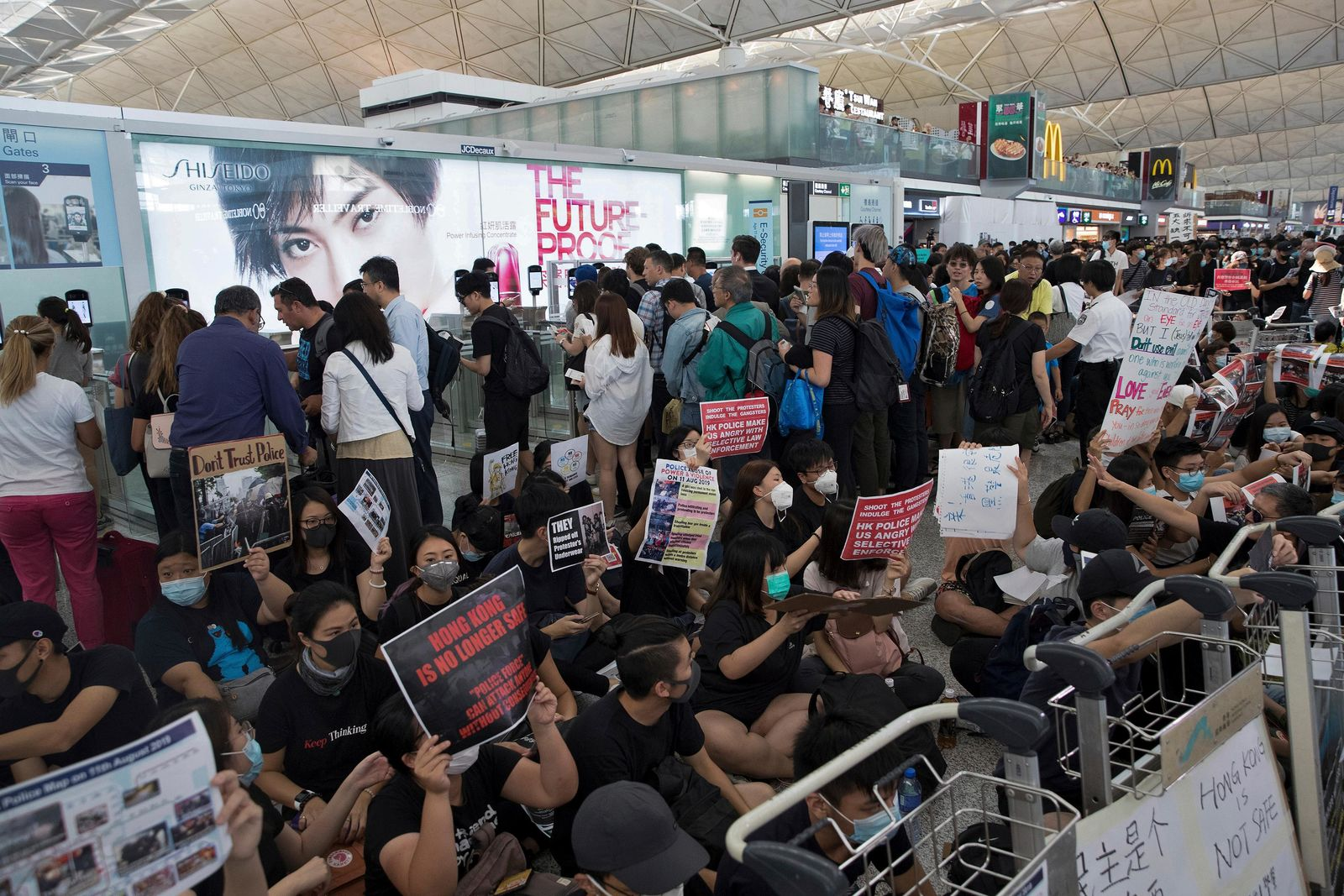 Travelers walk past as protesters hold a sit-in rally near the departure gate of the Hong Kong International Airport in Hong Kong, Tuesday, Aug. 13, 2019.{ } (AP Photo/Vincent Thian)