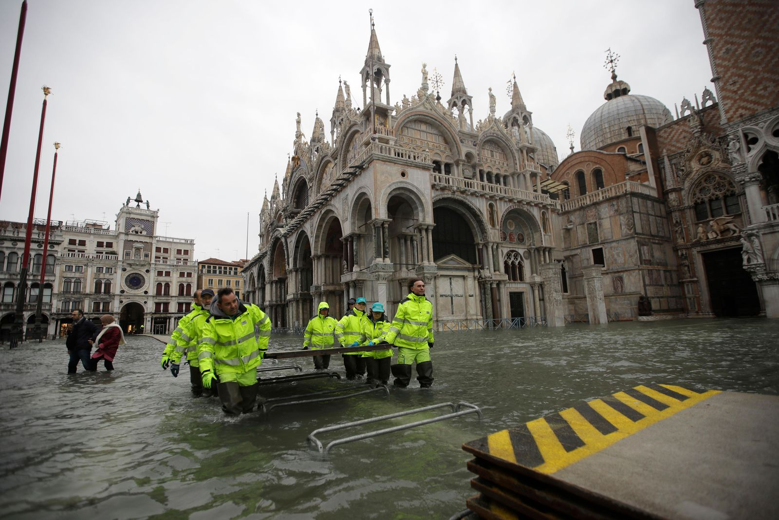 Municipality workers carry wooden boards to create a trestle bridge in a flooded St. Mark's Square at Venice, Friday, Nov. 15, 2019. (AP Photo/Luca Bruno)