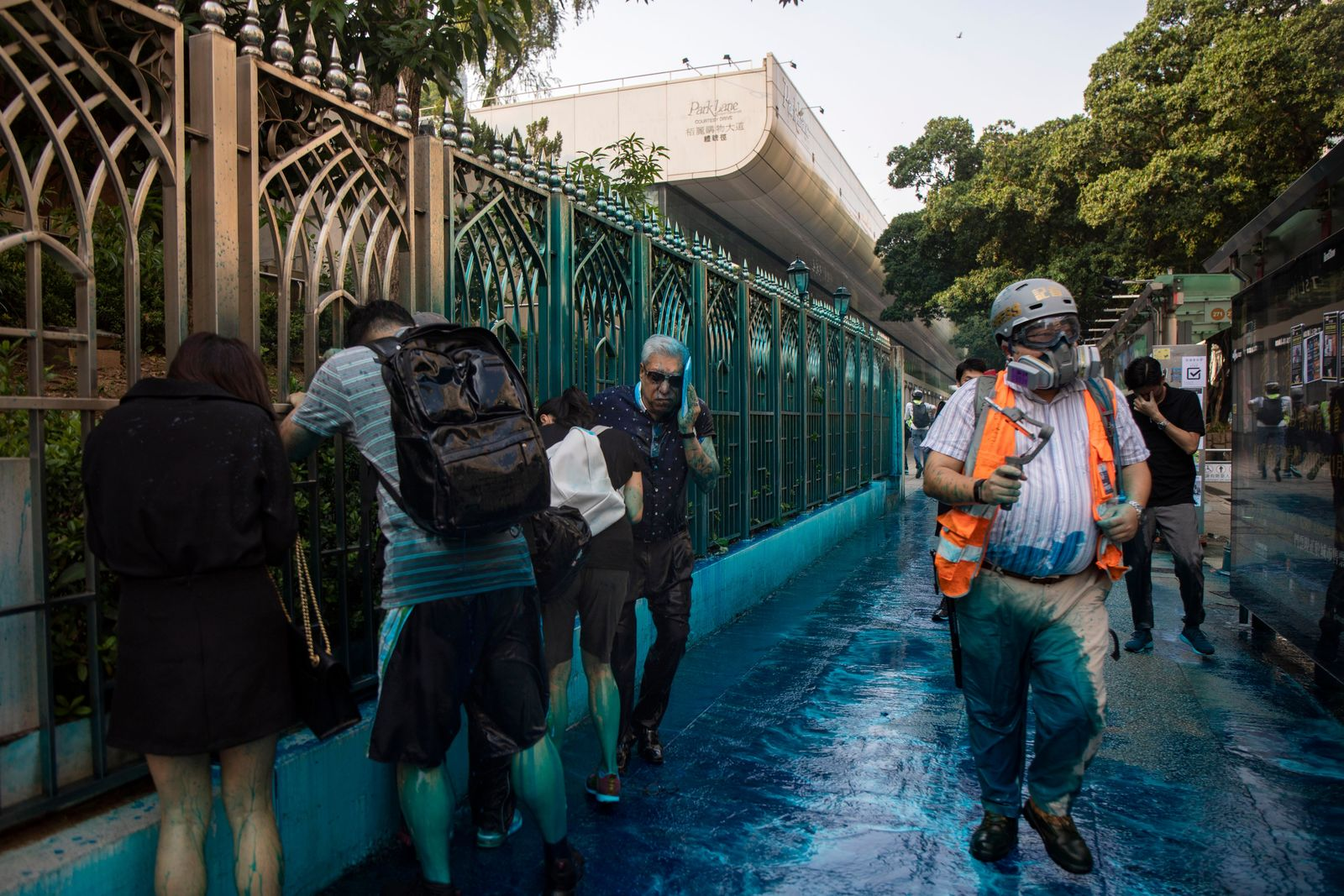 In this Sunday, Oct. 20, 2019 photo, people react after sprayed with blue-dyed water by a police riot-control vehicle during a protest outside the Kowloon Mosque in Hong Kong. (Chan Cheuk Fai/The Initium via AP)