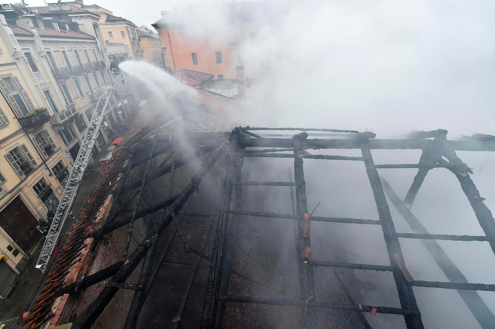 Firefighters put out a fire on the rooftop of the Cavallerizza Reale, in Turin, northern Italy, Monday, Oct. 21, 2019.{ } (Alessandro Di Marco/ANSA via AP)