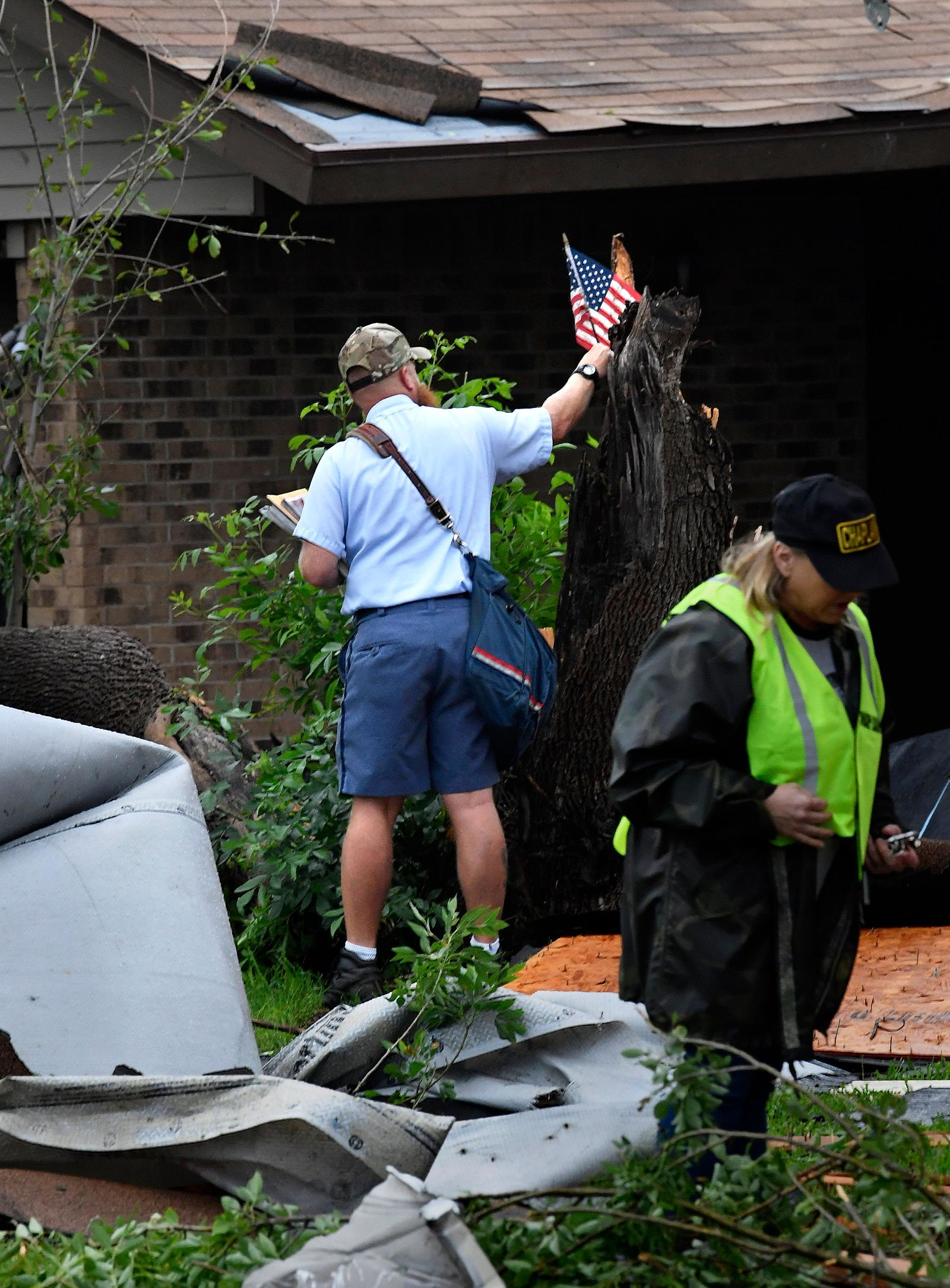 Letter carrier James Hurtado resets a small U.S. flag into a tree stump while delivering the mail Saturday May 18, 2019 on S. 6th St. in Abilene. Strong winds decimated the area in the early morning hours. AP photo by Ronald W. Erdrich, Abilene Reporter-News. Credit must appear./The Abilene Reporter-News via AP)