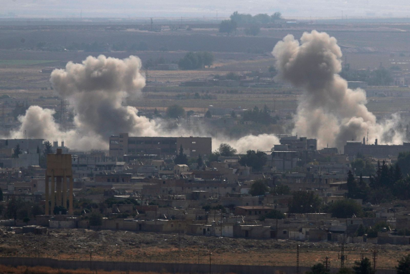 In this photo taken from the Turkish side of the border between Turkey and Syria, in Ceylanpinar, Sanliurfa province, southeastern Turkey, smoke and dust billows from targets in Ras al-Ayn, Syria, caused by bombardment by Turkish forces, Tuesday, Oct. 15, 2019. (AP Photo/Lefteris Pitarakis)