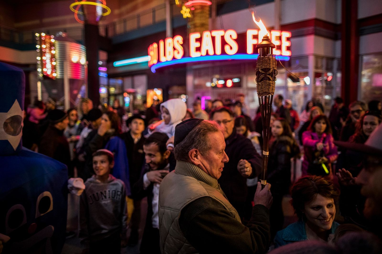 The torch is walked through the crowds before lighting Grand Menorah in downtown Las Vegas on Sunday, Dec. 2. The Grand Menorah will remain on display throughout the Hanukkah season. CREDIT: Joe Buglewicz/Las Vegas News Bureau