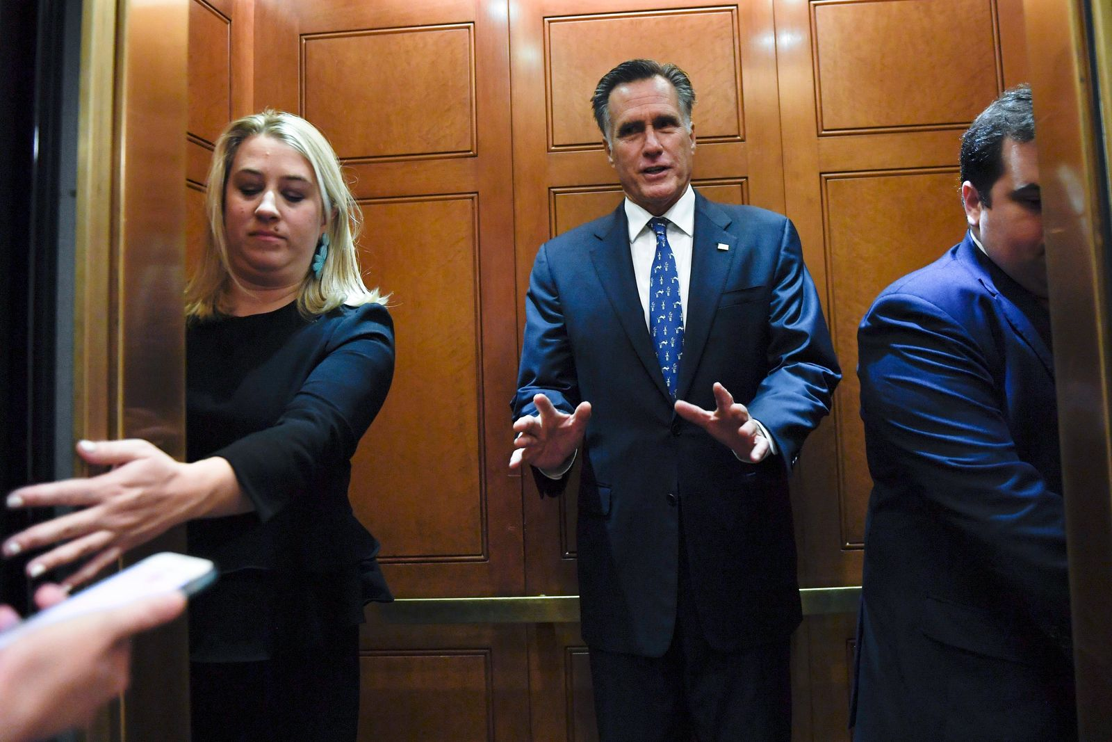 FILE - In this Nov. 5, 2019, file photo, Sen. Mitt Romney, R-Utah, gets in an elevator as he is followed by reporters on Capitol Hill in Washington. Republicans have no unified argument in the impeachment inquiry of Donald Trump in large part because they can't agree on how to defend the president.  (AP Photo/Susan Walsh, File)