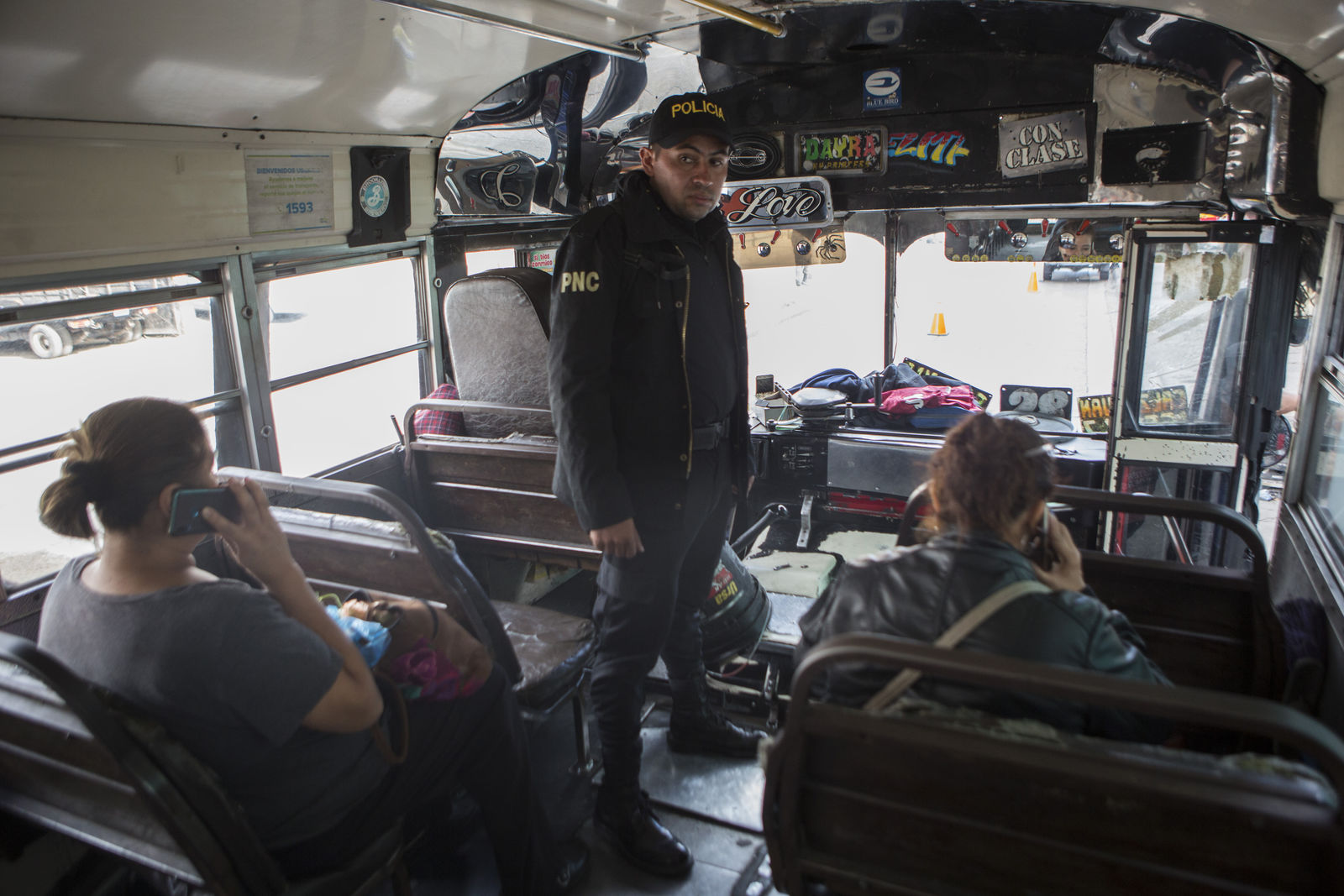 A police officer stands inside a bus after it was stopped to search its passengers at a security checkpoint in the El Milagro area of the Mixco municipality on the outskirts of Guatemala City, Friday, Jan. 17, 2020. Guatemala's new president announced a state of alert for two municipalities with high crime rates to combat gang activity Friday, a measure that allows the deployment of military troops. (AP Photo/Oliver de Ros)