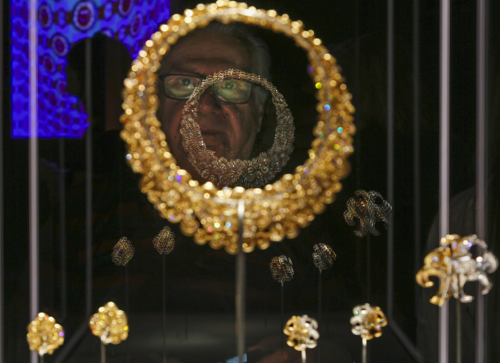 "A man looks at a Bulgari necklace and earrings in gold with diamonds from 1969 during a preview of the exhibition ""Bulgari.{ } (AP Photo/Domenico Stinellis)"