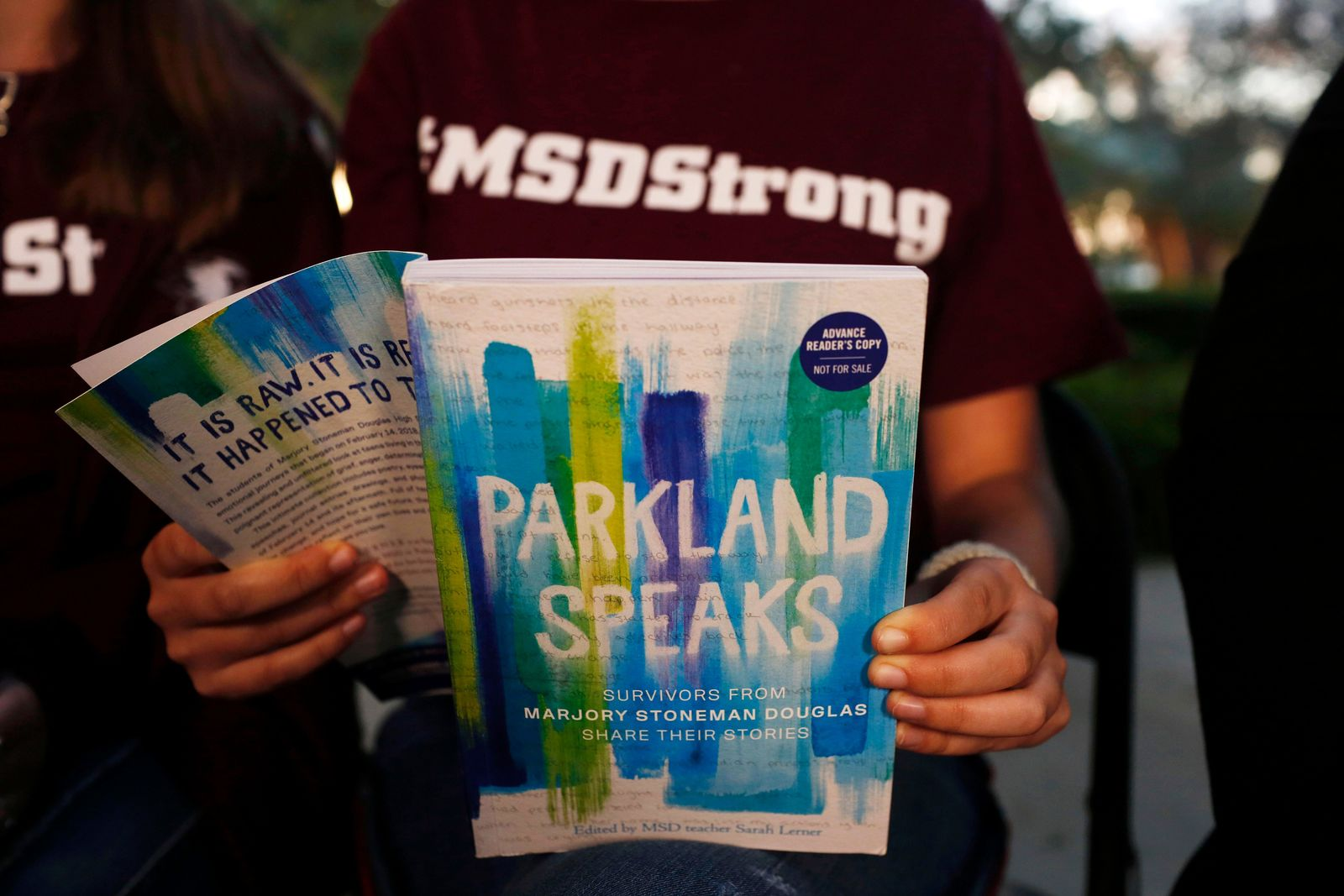 "In this Wednesday, Jan. 16, 2019, photo, Leni Steinhardt, 16, reads from a new book called ""Parkland Speaks: Survivors from Marjory Stoneman Douglas Share Their Stories,"" during an interview with The Associated Press, in Parkland, Fla. (AP Photo/Brynn Anderson)"