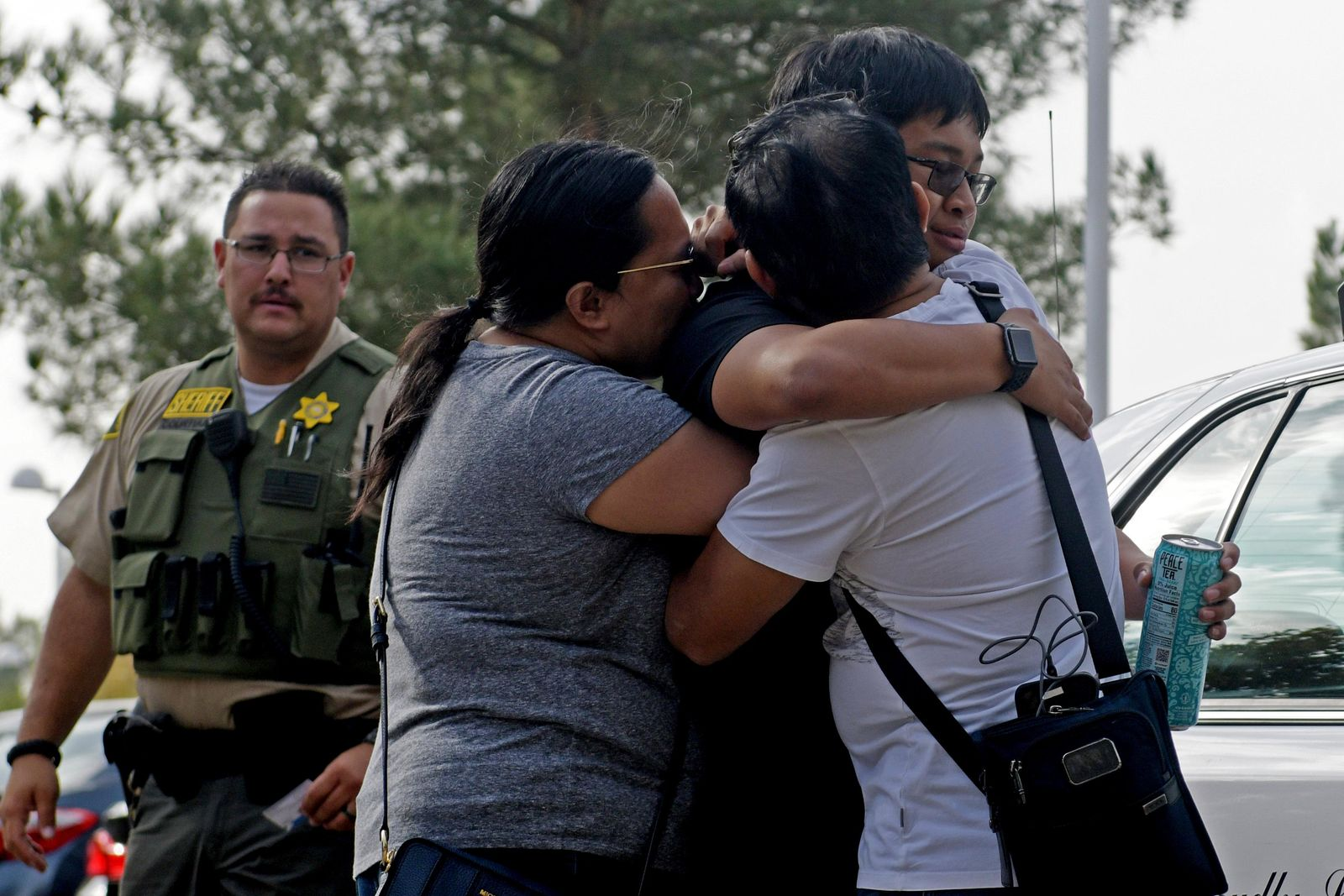 Bernadette and Joy Song Cuan hug their son Karl, a witness to the shooting at Saugus High School, after being interviewed by law enforcement on Thursday, Nov. 14, 2019 in Santa Clarita, Calif. The shooting occurred around 7:30 a.m. at the high school, about 30 miles northwest of downtown Los Angeles (AP Photo by Christian Monterrosa)