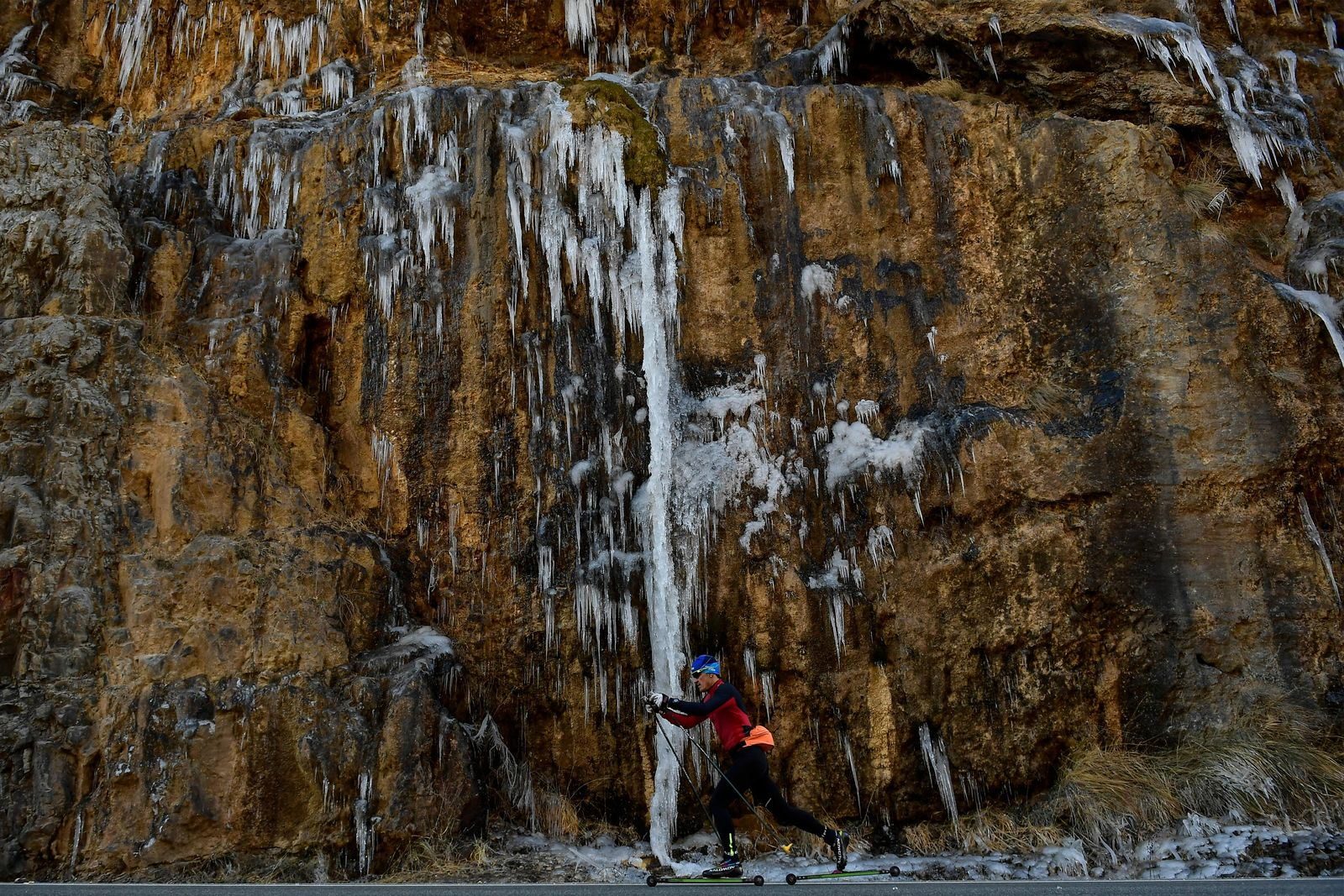 A man skis on the road while passing a stone wall covered with icicles near to the small Pyrenees town of El Roncal, northern Spain, Friday Jan. 11. (AP Photo/Alvaro Barrientos)