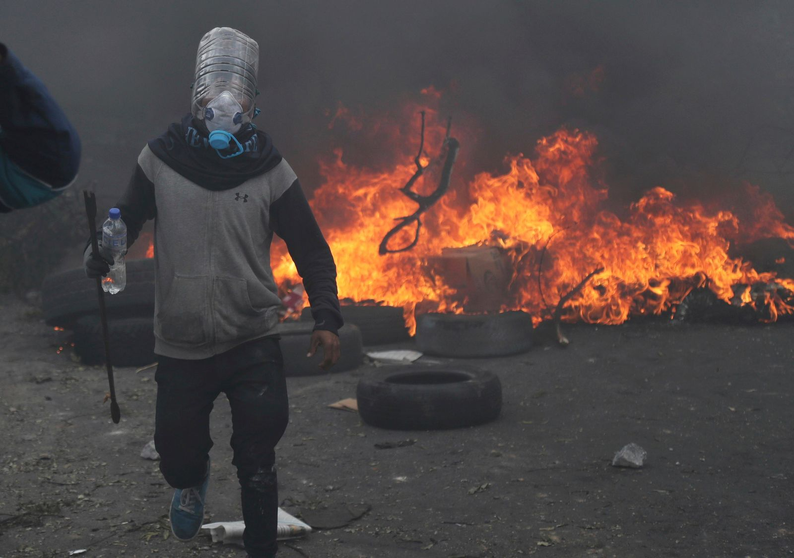 An anti-government demonstrator protects himself with a homemade gas mask during a clash with the police in Quito, Ecuador, Saturday, Oct. 12, 2019. (AP Photo/Dolores Ochoa)
