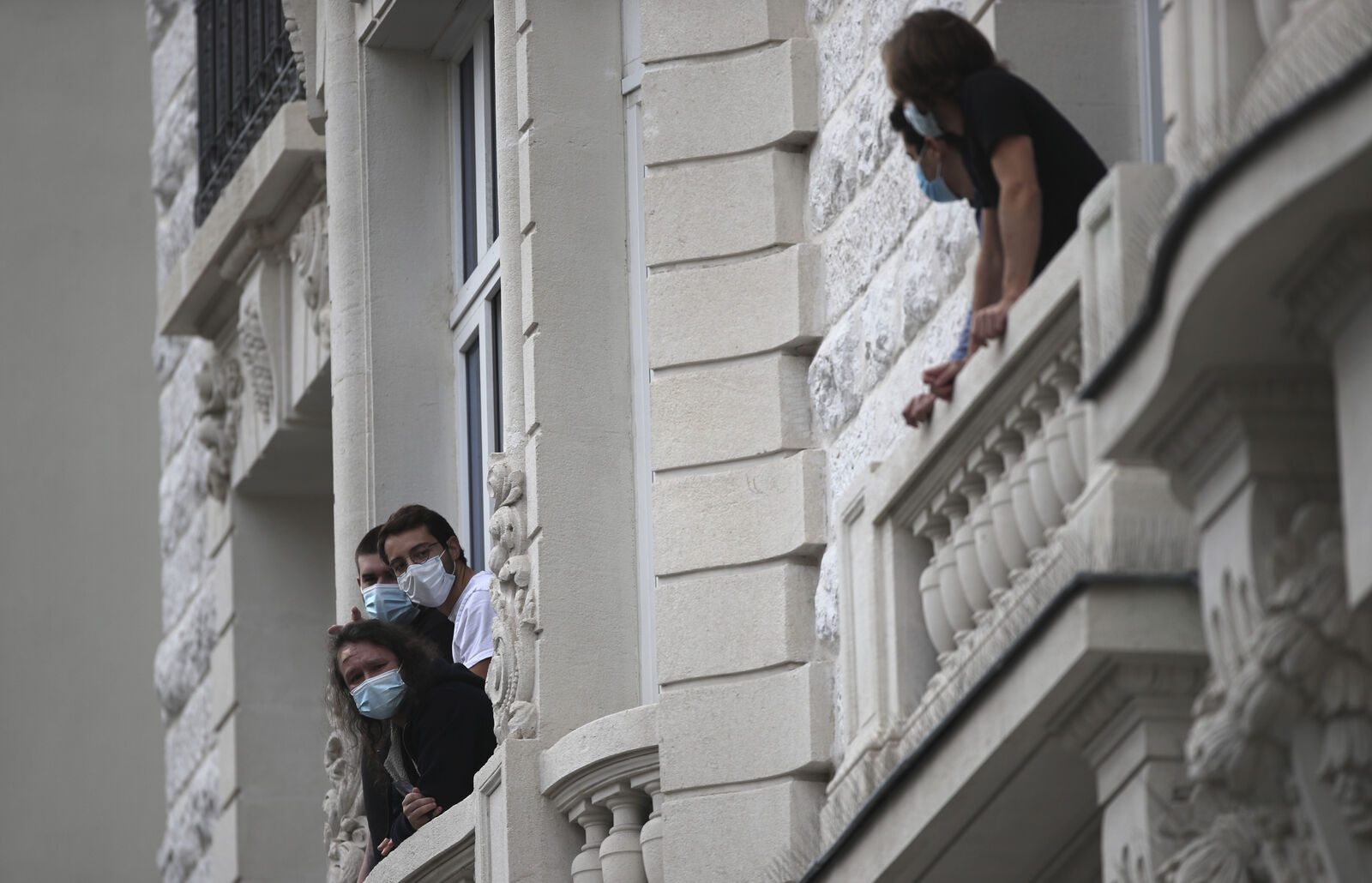 FILE- Residents look out of their windows near the Notre Dame church in Nice, southern France, after a knife attack took place on Thursday, Oct. 29, 2020.{ } (AP Photo/Daniel Cole)
