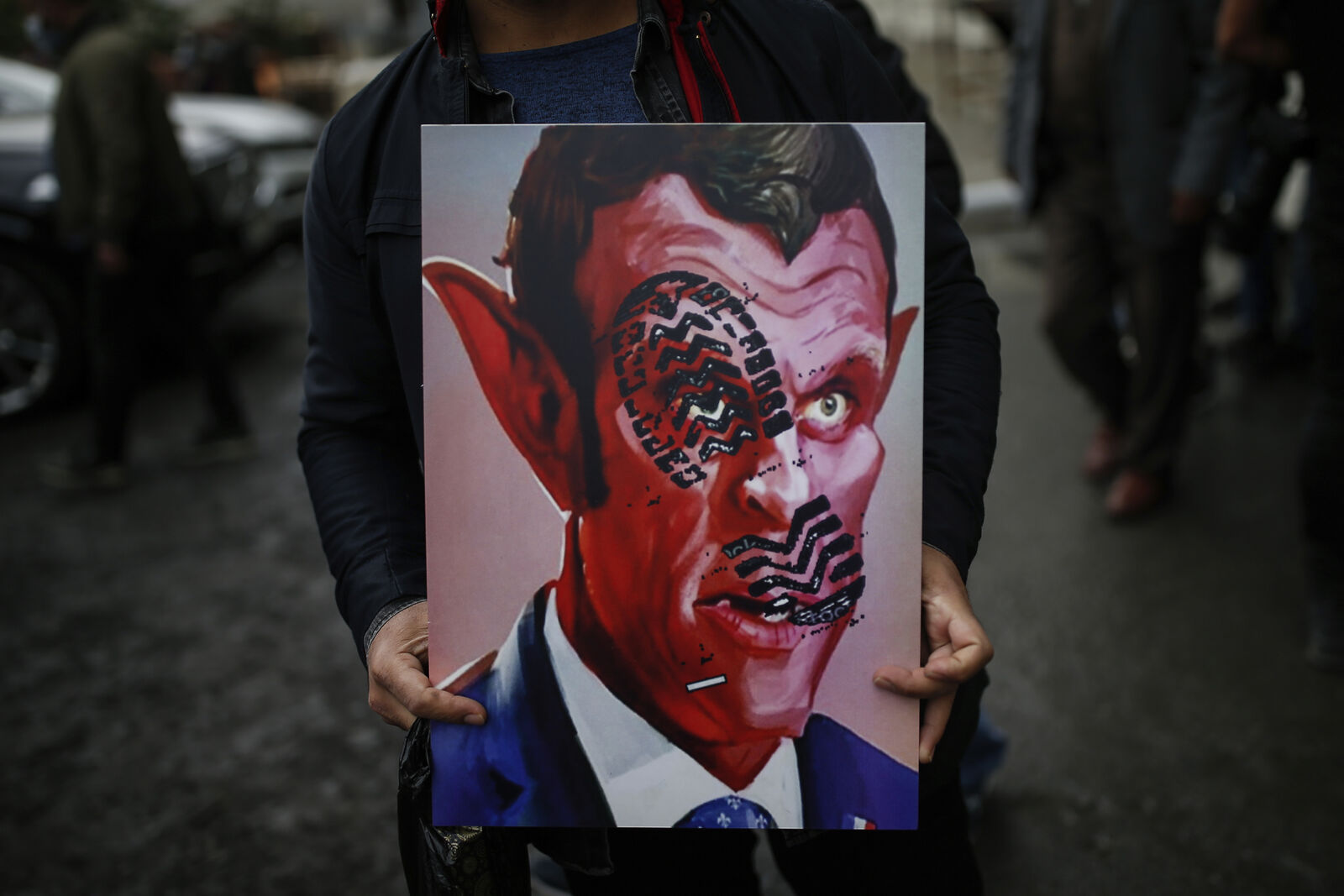 A man holds a poster with a caricature of France's President Emmanuel Macron, depicting him as devil during a protest against France in Istanbul, Friday, Oct. 30, 2020. (AP Photo/Emrah Gurel)